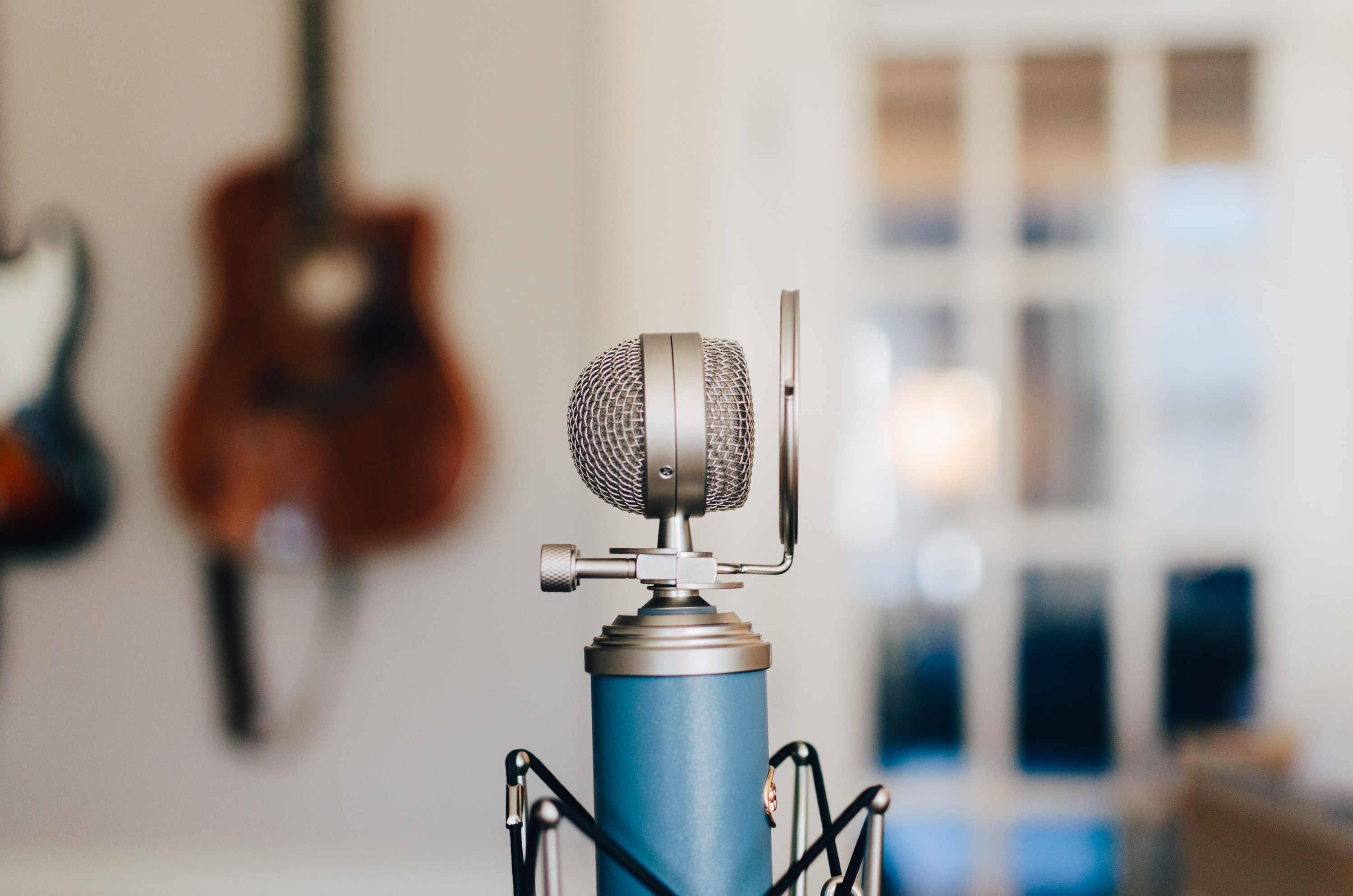 A small bluebird microphone on a stand with a pop filter in a white, bright room with hanging guitars