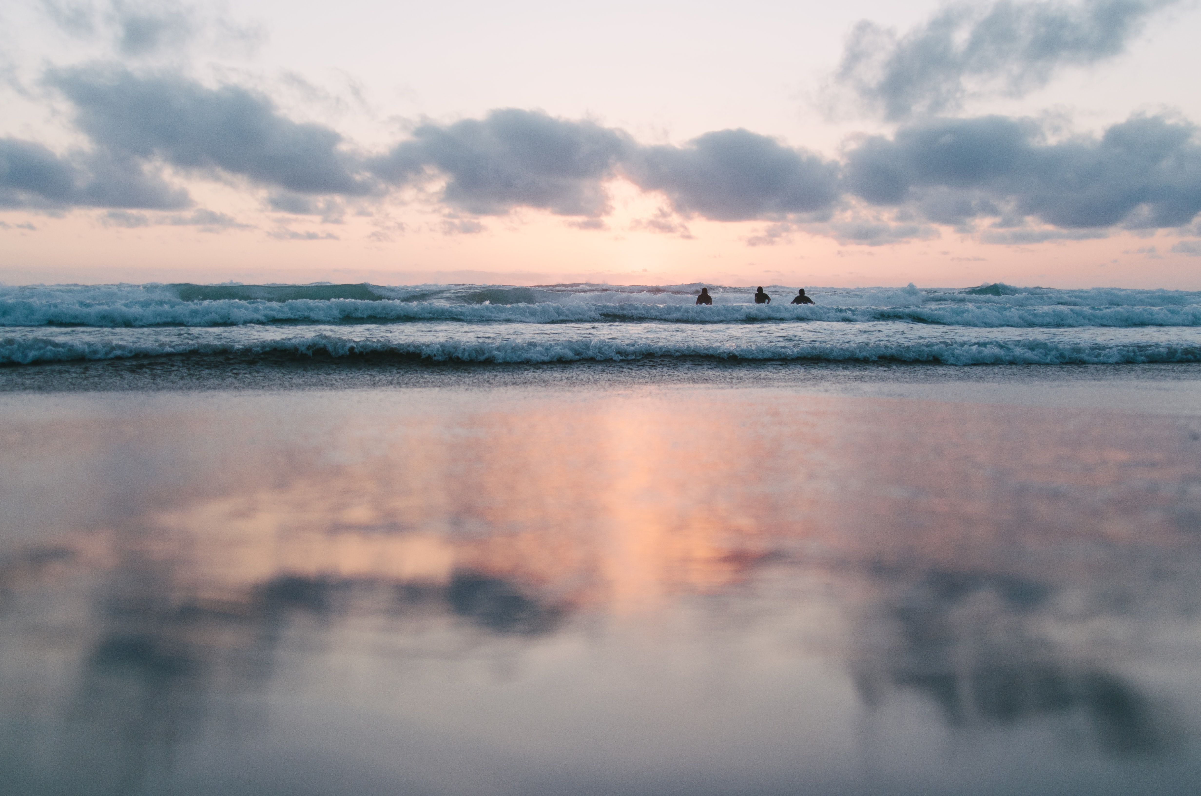 Three people in ocean waves, with a blurred reflection of a partly cloudy pastel sunset in the foreground