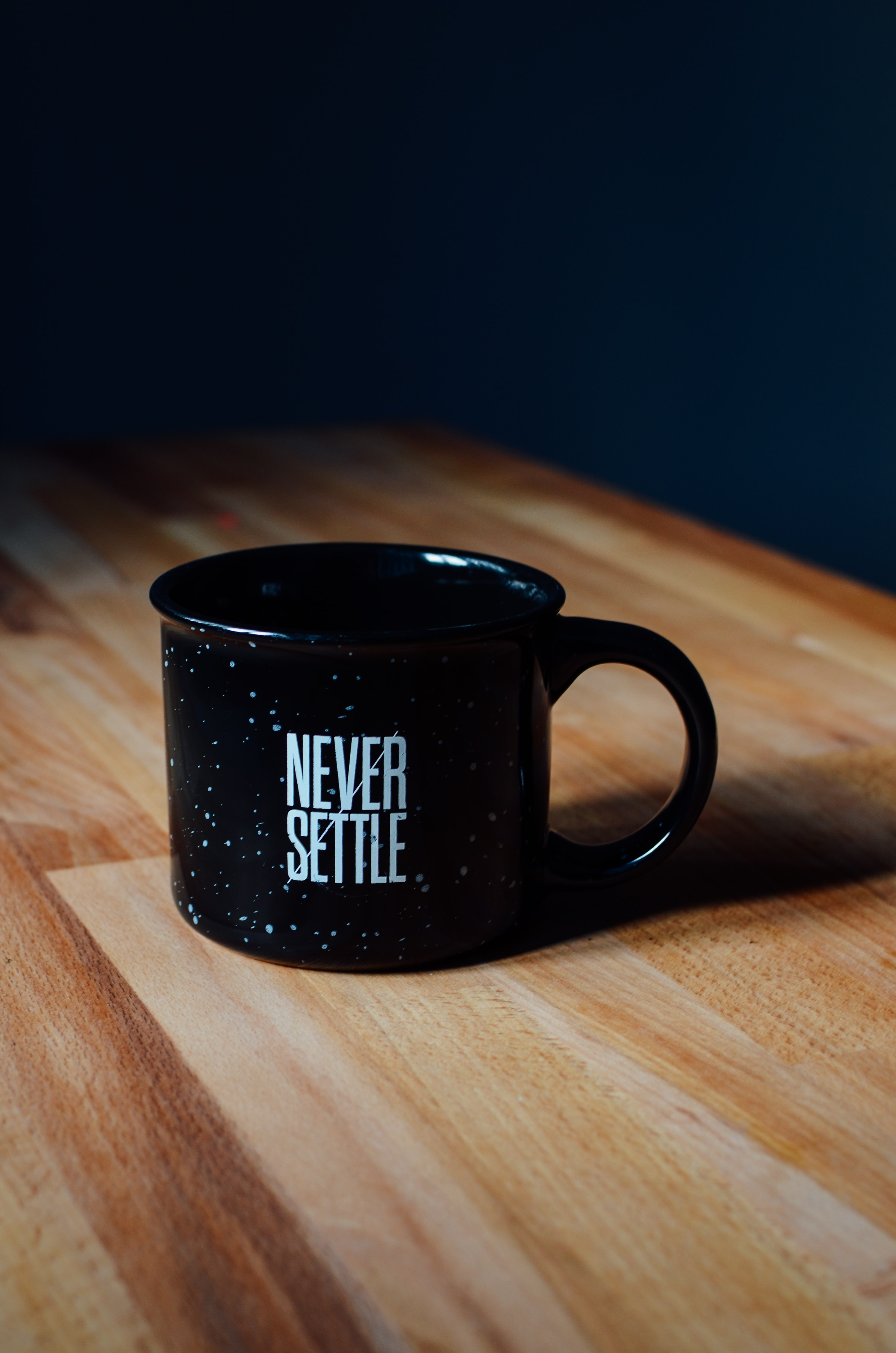 "A black enamel mug with a ""never settle"" print"