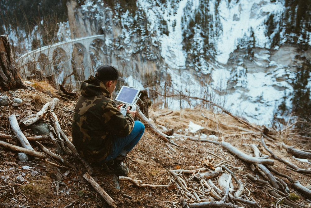 man holding white tablet computer outdoor
