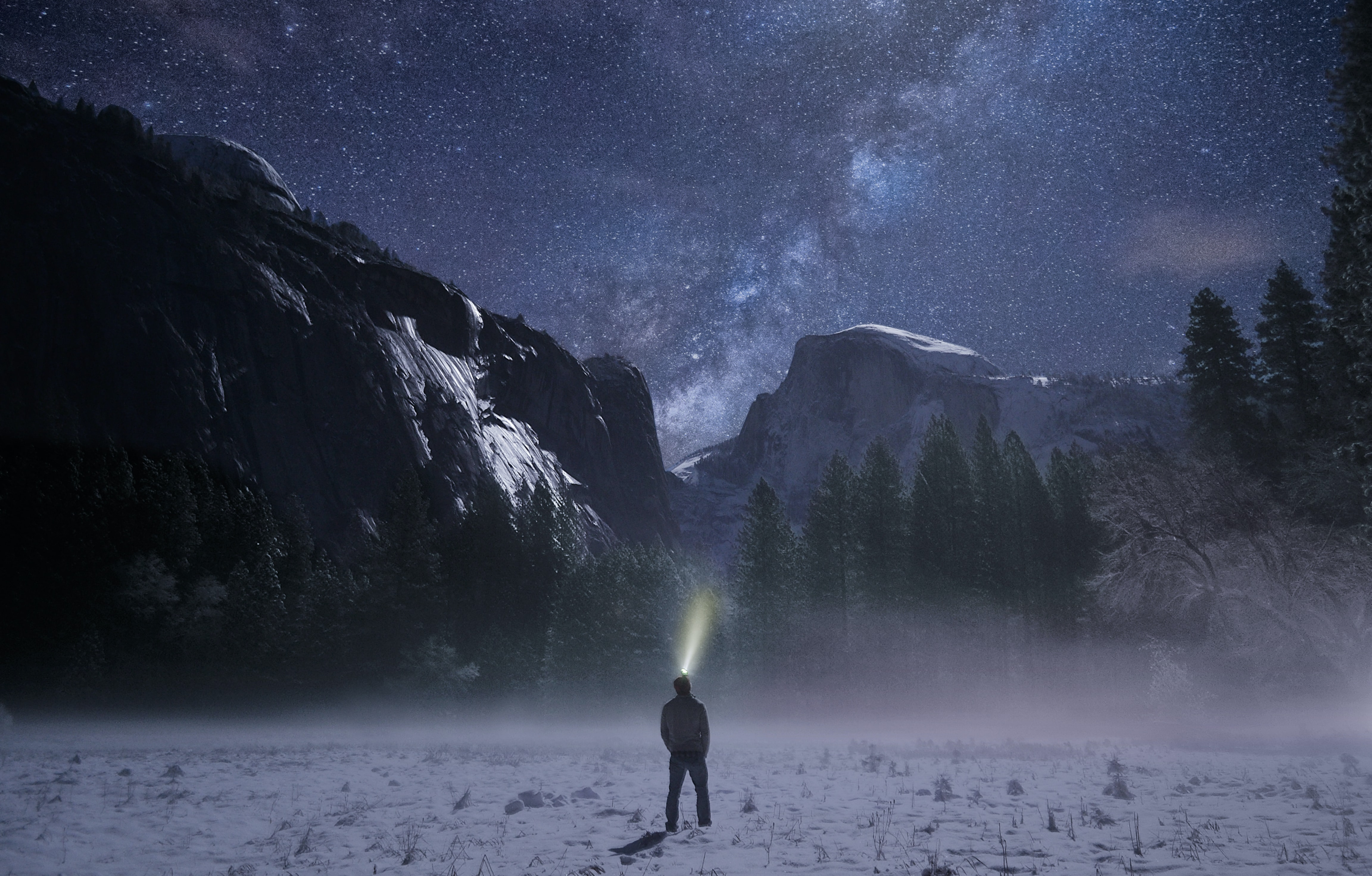 person wearing headlamp facing towards snow mountain