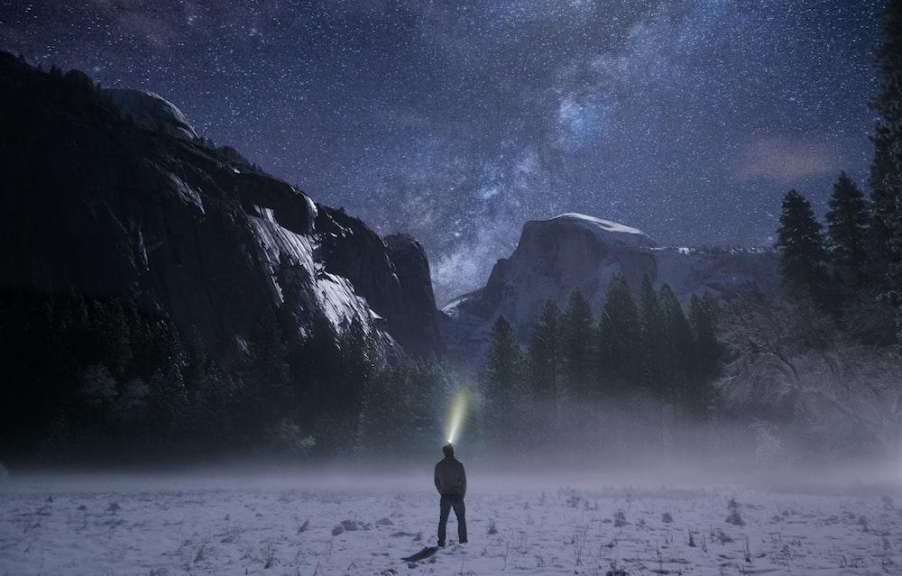 person wearing headlamp facing towards snow mountain
