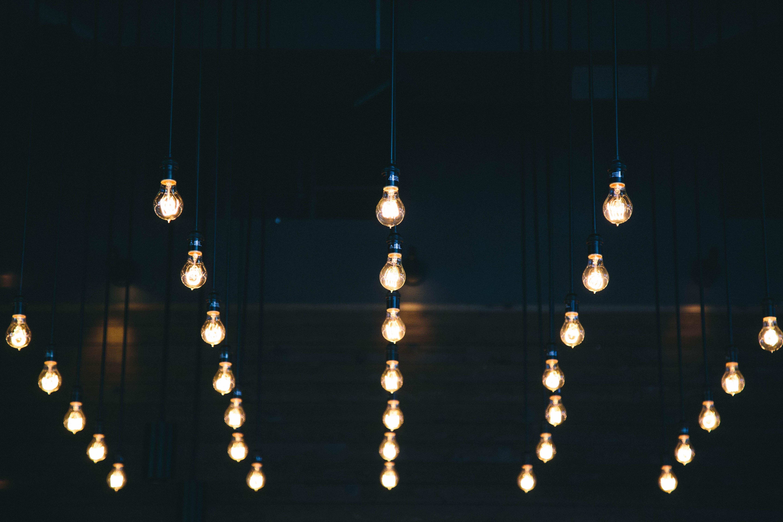 Rows of glowing light bulbs in a dark room