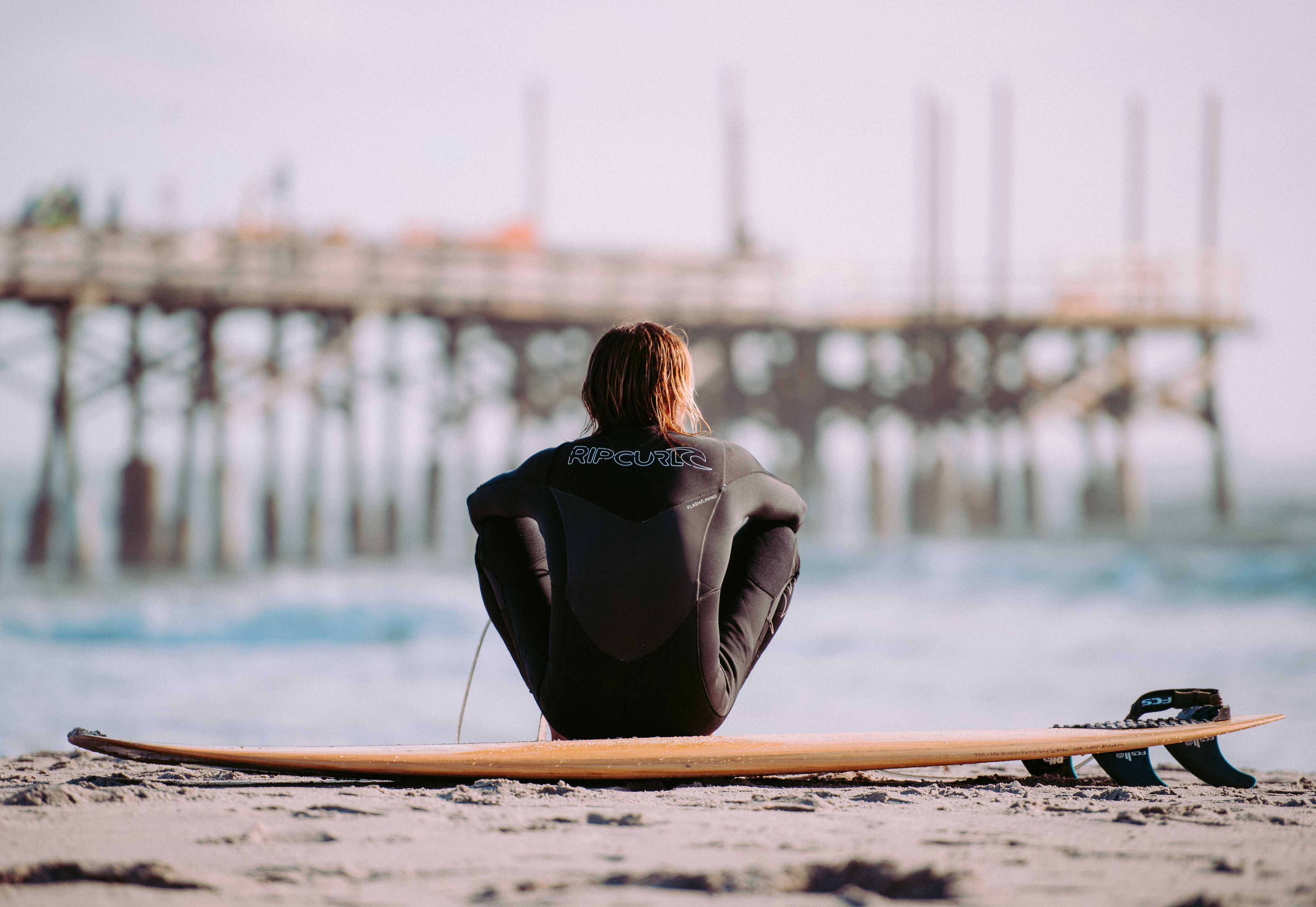 Surfer in a wetsuit sitting on the beach by the surfboard at Cocoa Beach
