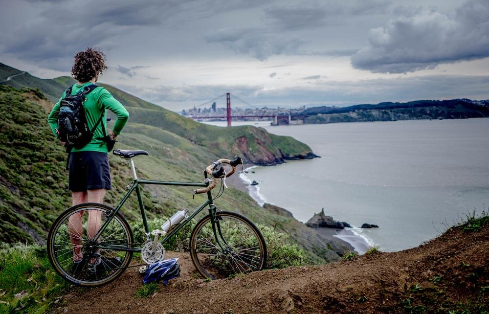 man standing beside bike on top of mountain