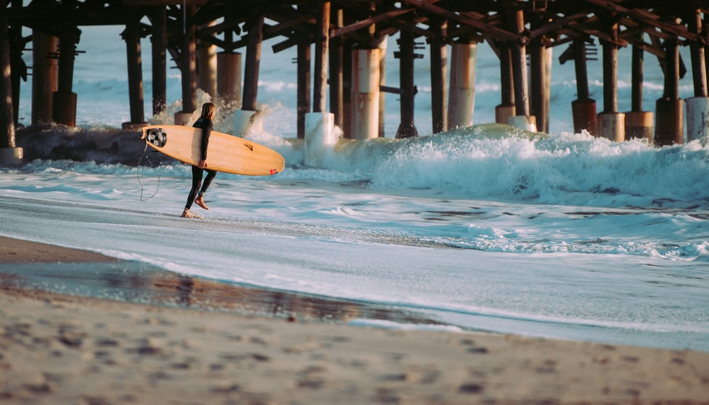 person holding surfboard standing on seashore in front of wave near wooden dock