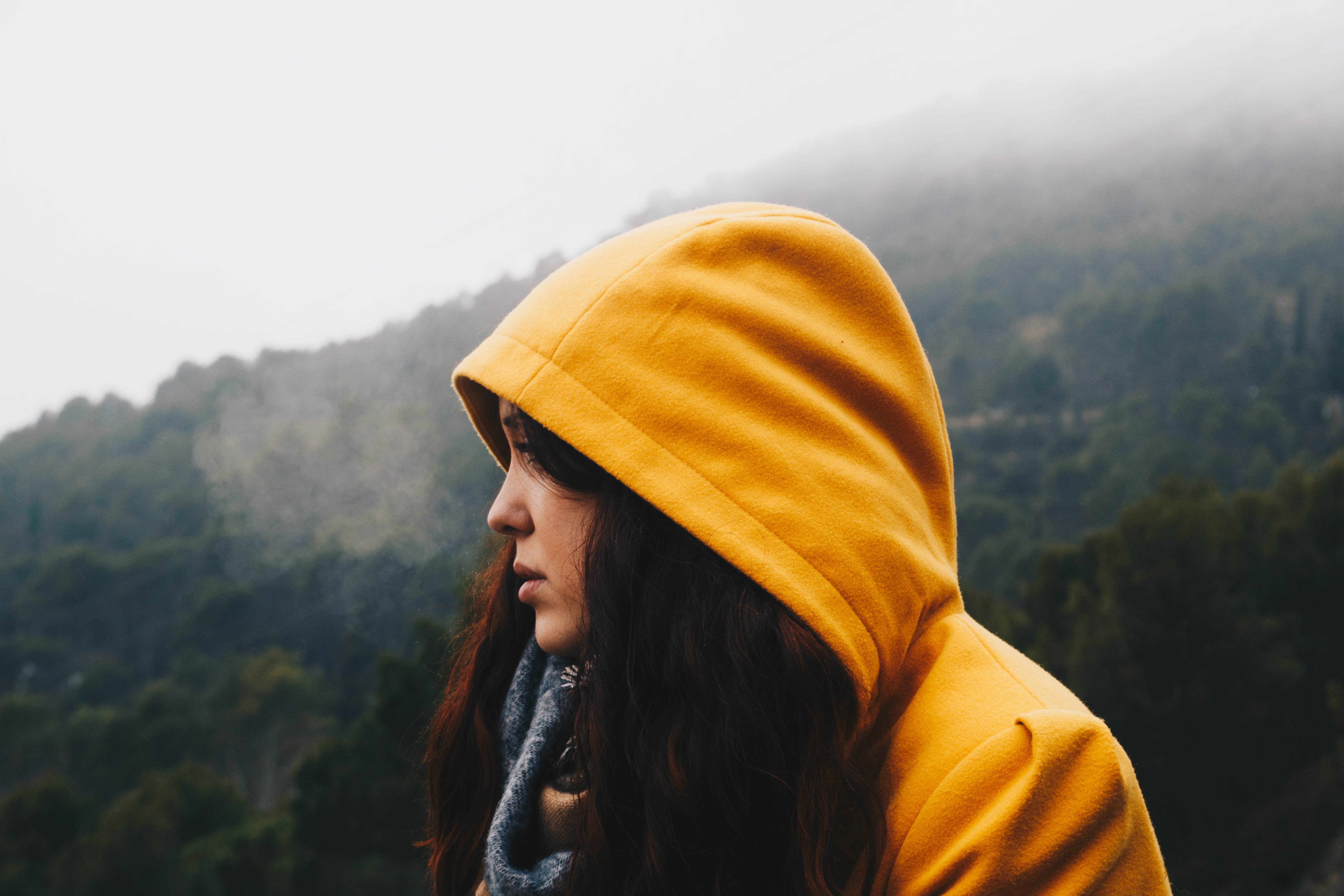 A dark-haired woman in a yellow hood against a backdrop of mountain forests