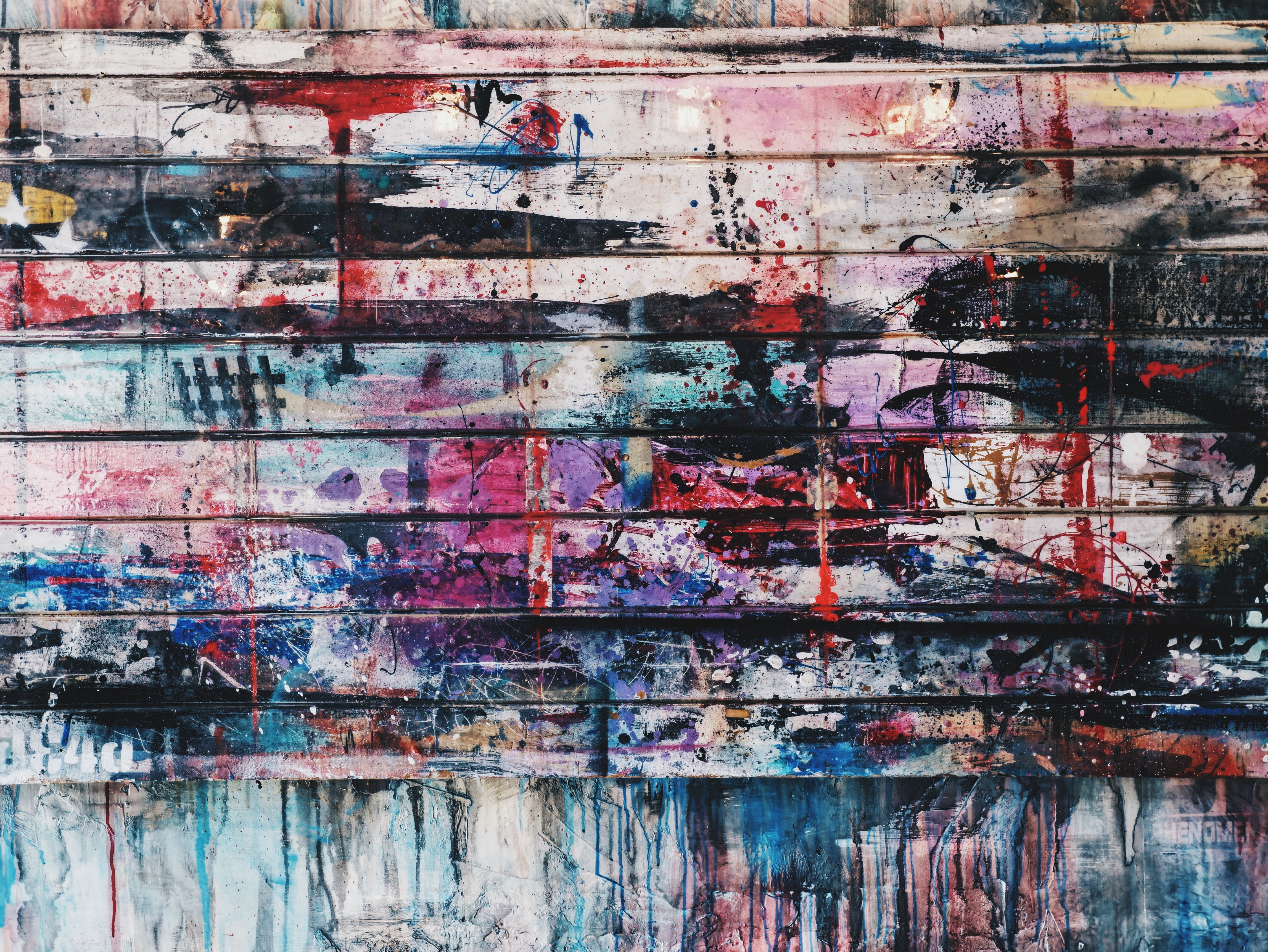 Splattered colors of paint on a paneled wall