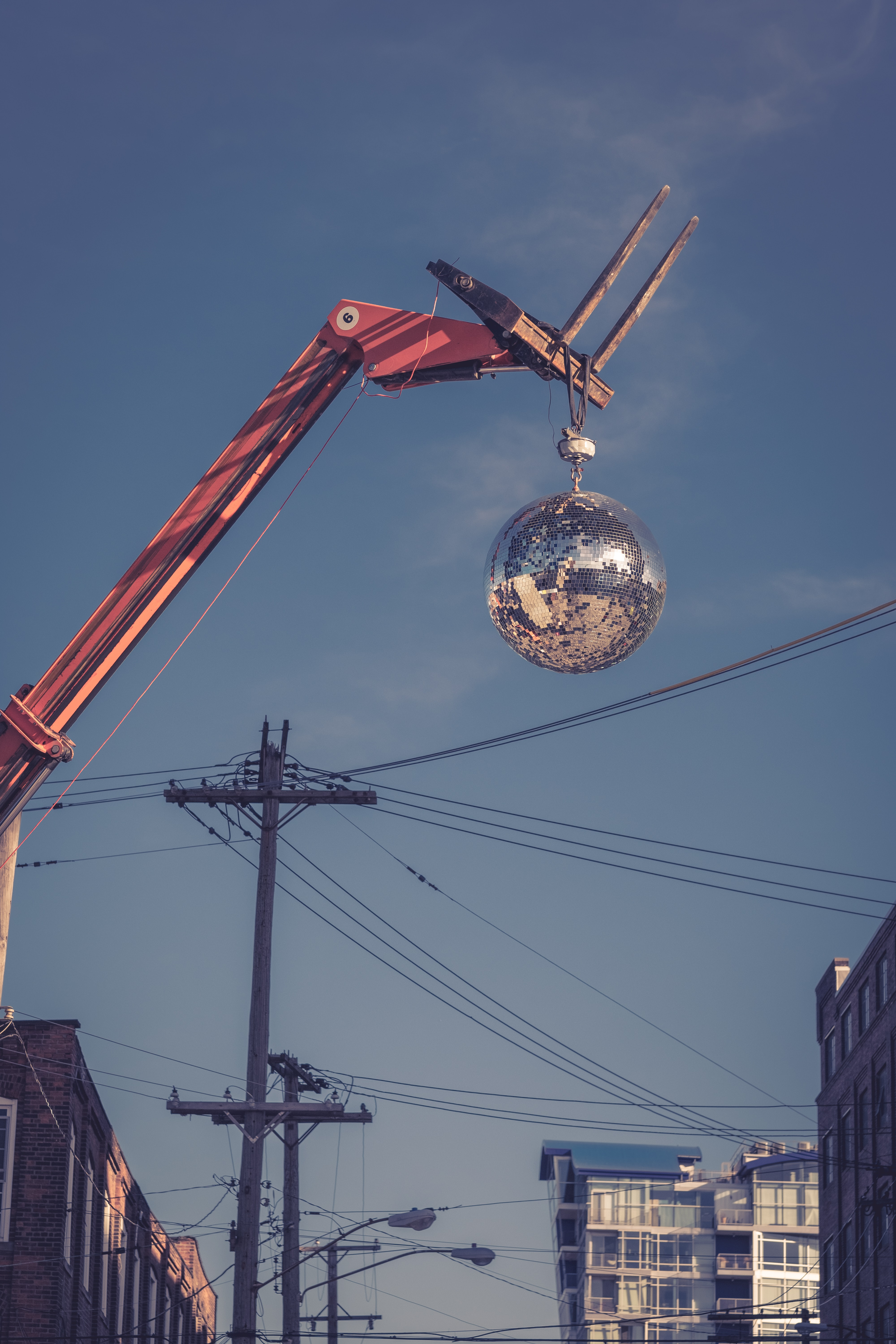 worm's-eye view photography of red and silver wrecking ball near electric post under clear blue sky