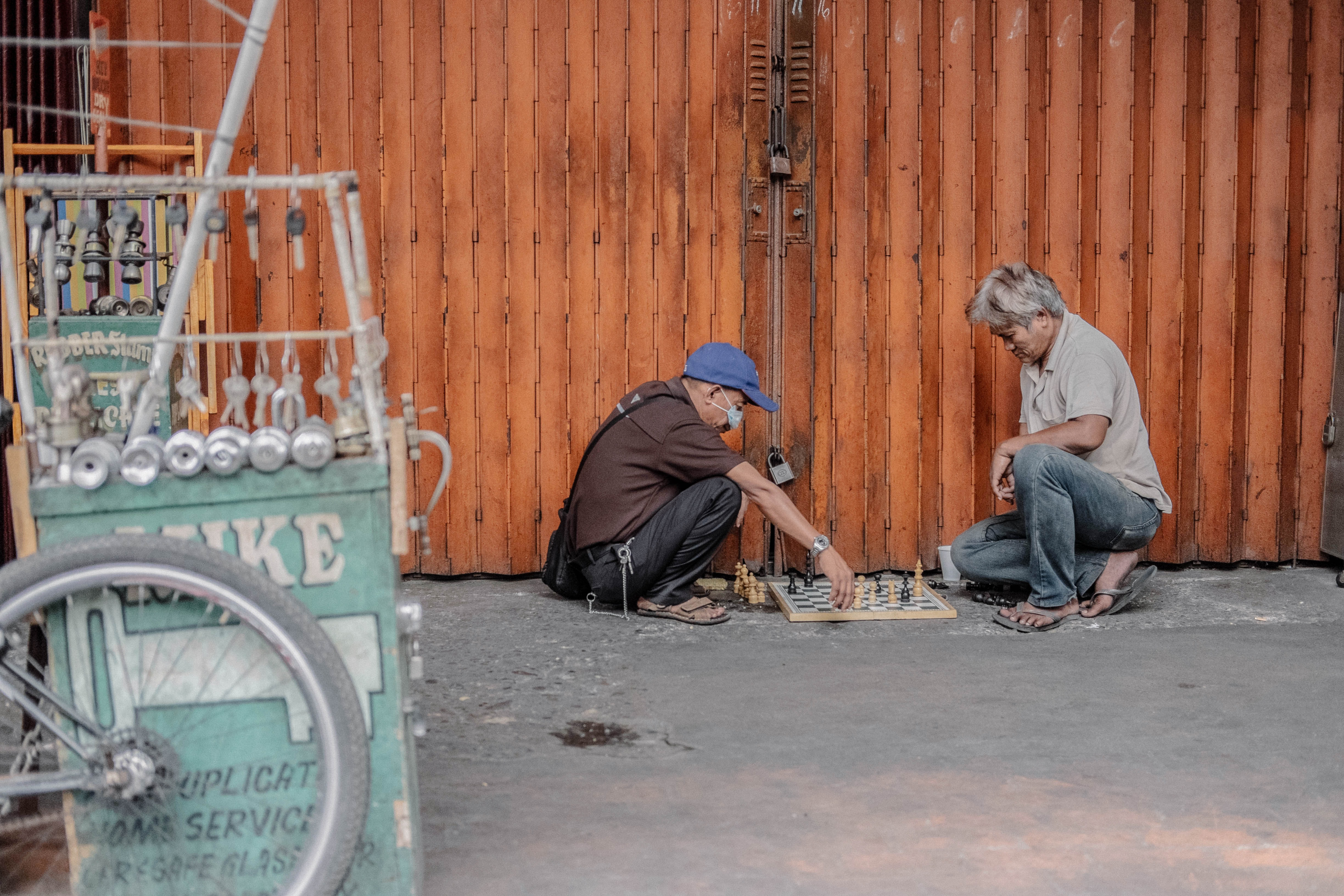 Two men playing chess while sitting on the floor in front of a red building, next to a bike store