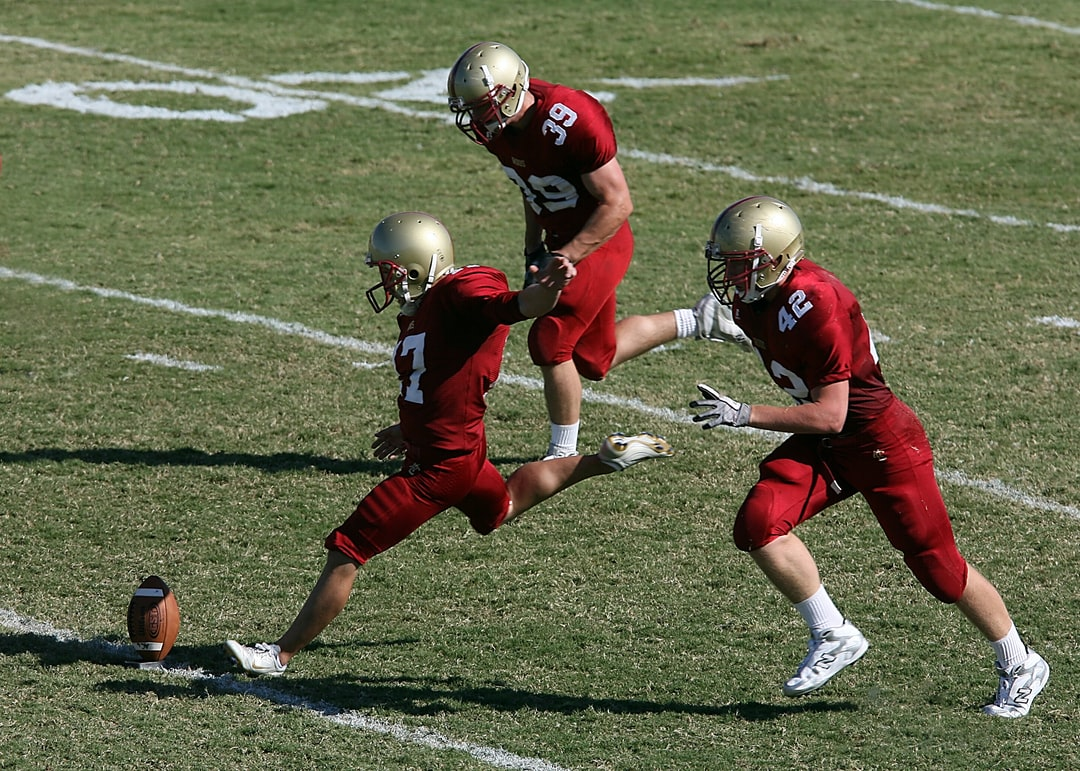 College player prepares to kick the ball to start the game.  His teammates prepare to accompany him downfield.