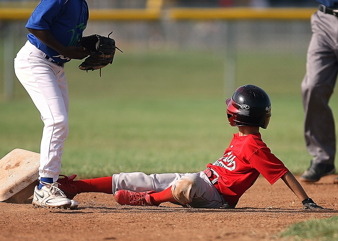 Little league ball player looks to the umpire for a ruling after sliding into second base.