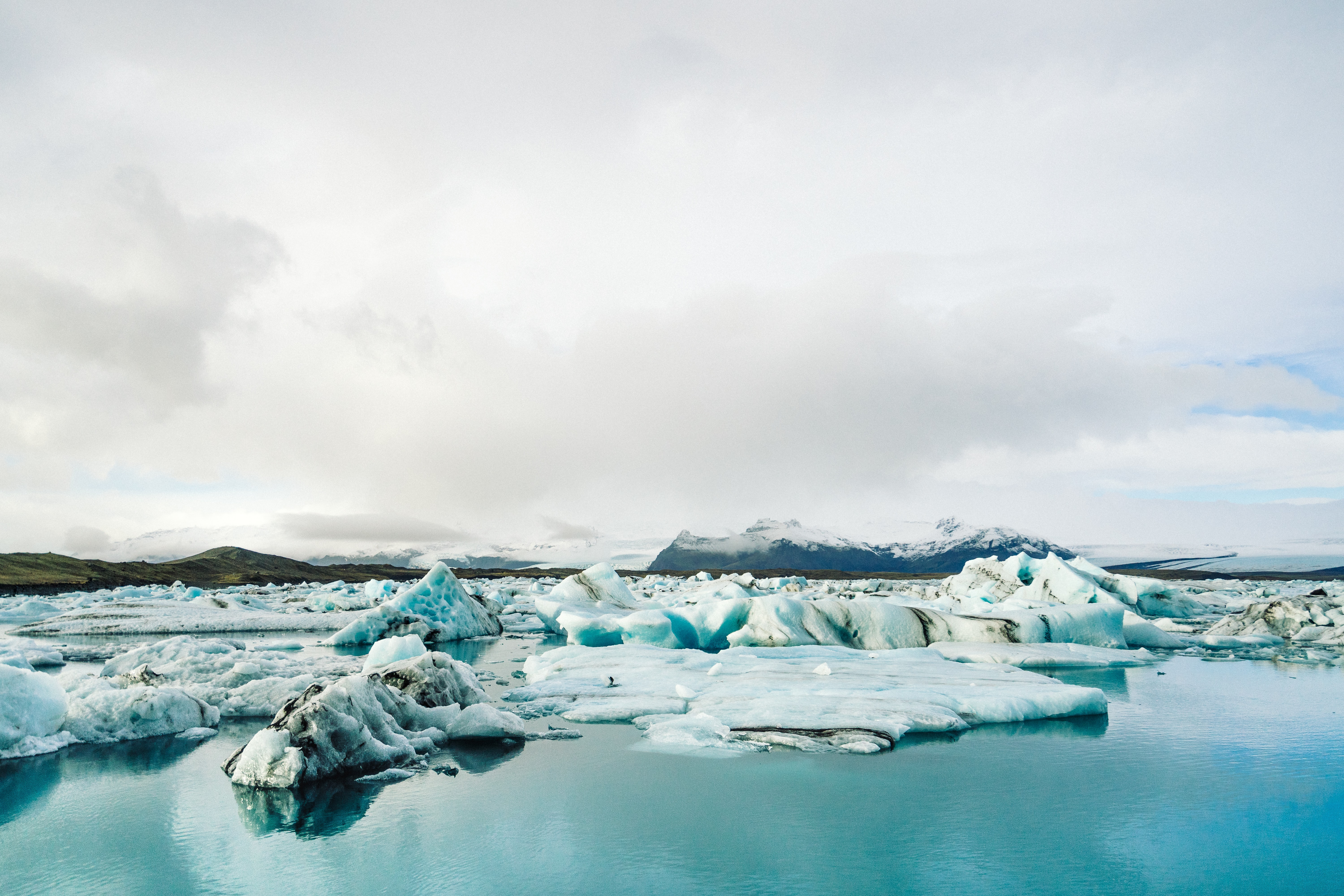 Small icebergs in bright turquoise blue water with thick clouds above
