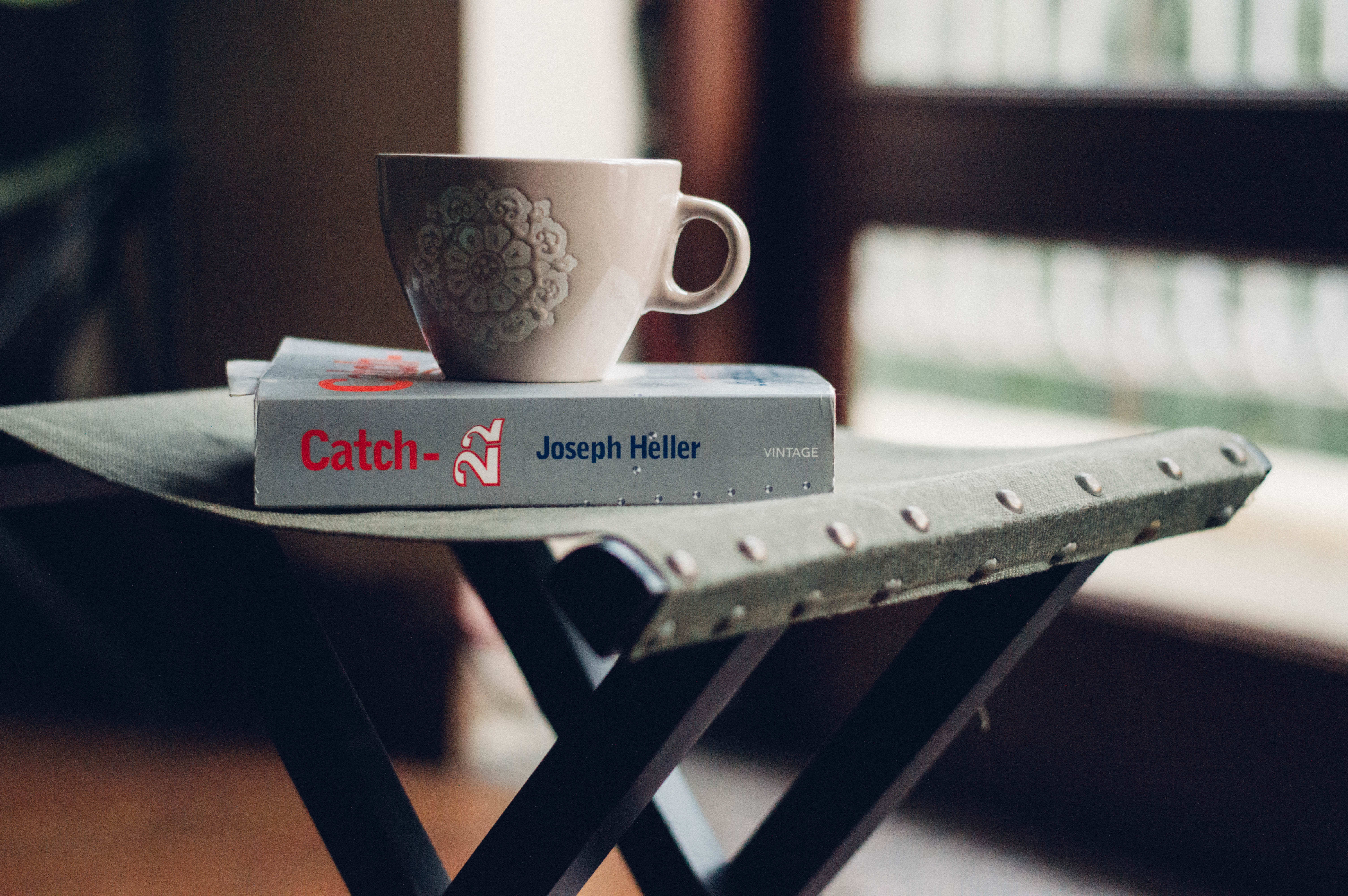 close-up photography of beige ceramic coffee cup on top of Joseph Heller book