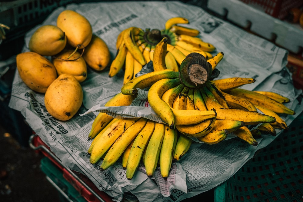 mangoes and bananas on newspaper