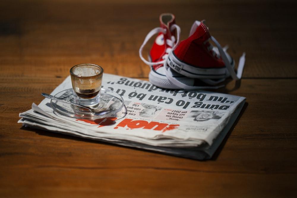 teacup on saucer on top of newspaper