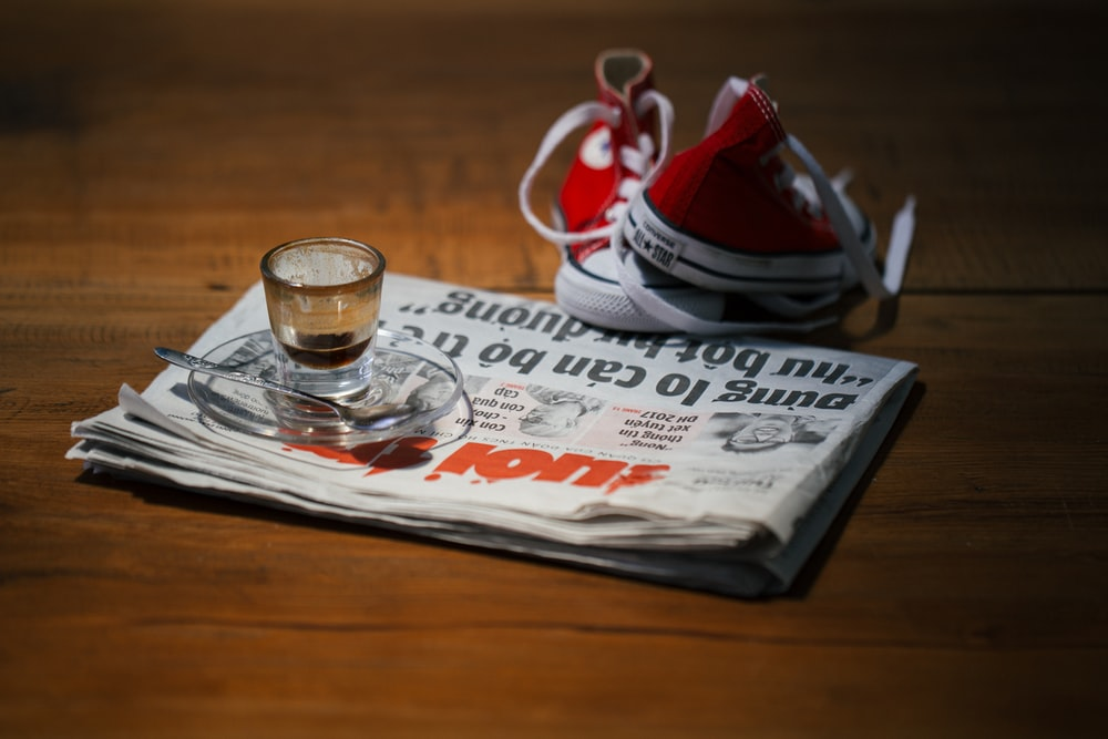 teacup on saucer on top of newspaper