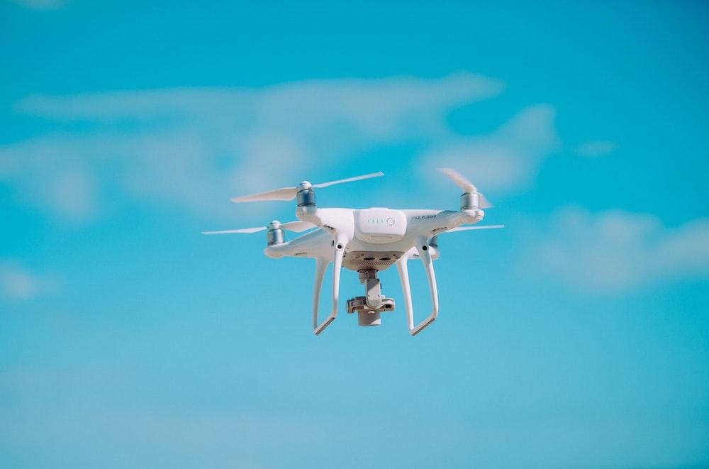 white quadcopter flying during daytime