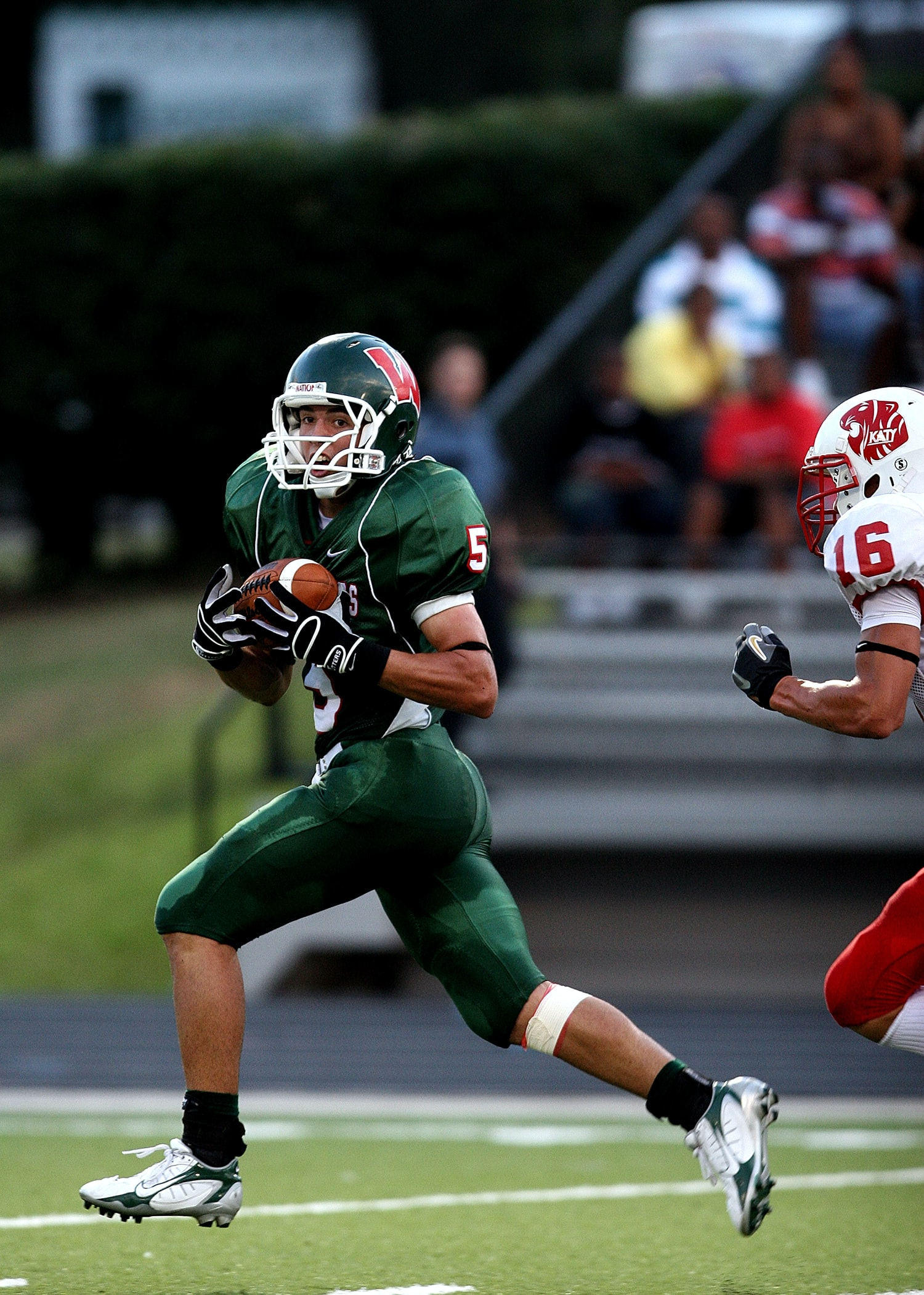 man in green 5 American football jersey holding ball