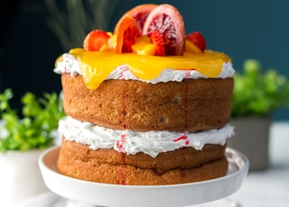 two-layered cake with citrus fruit and strawberry toppings