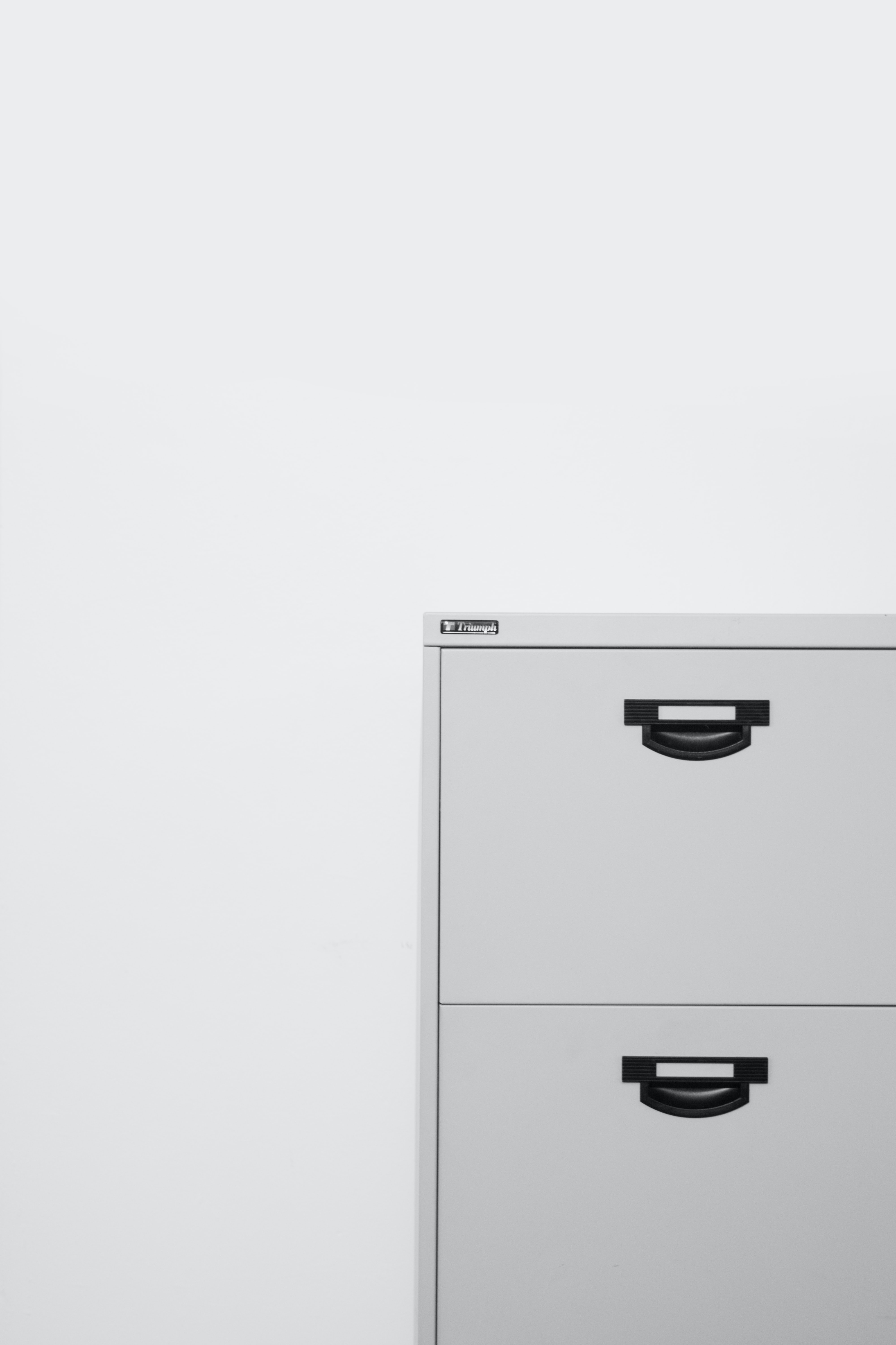 A white filing cabinet in front of a white wall.