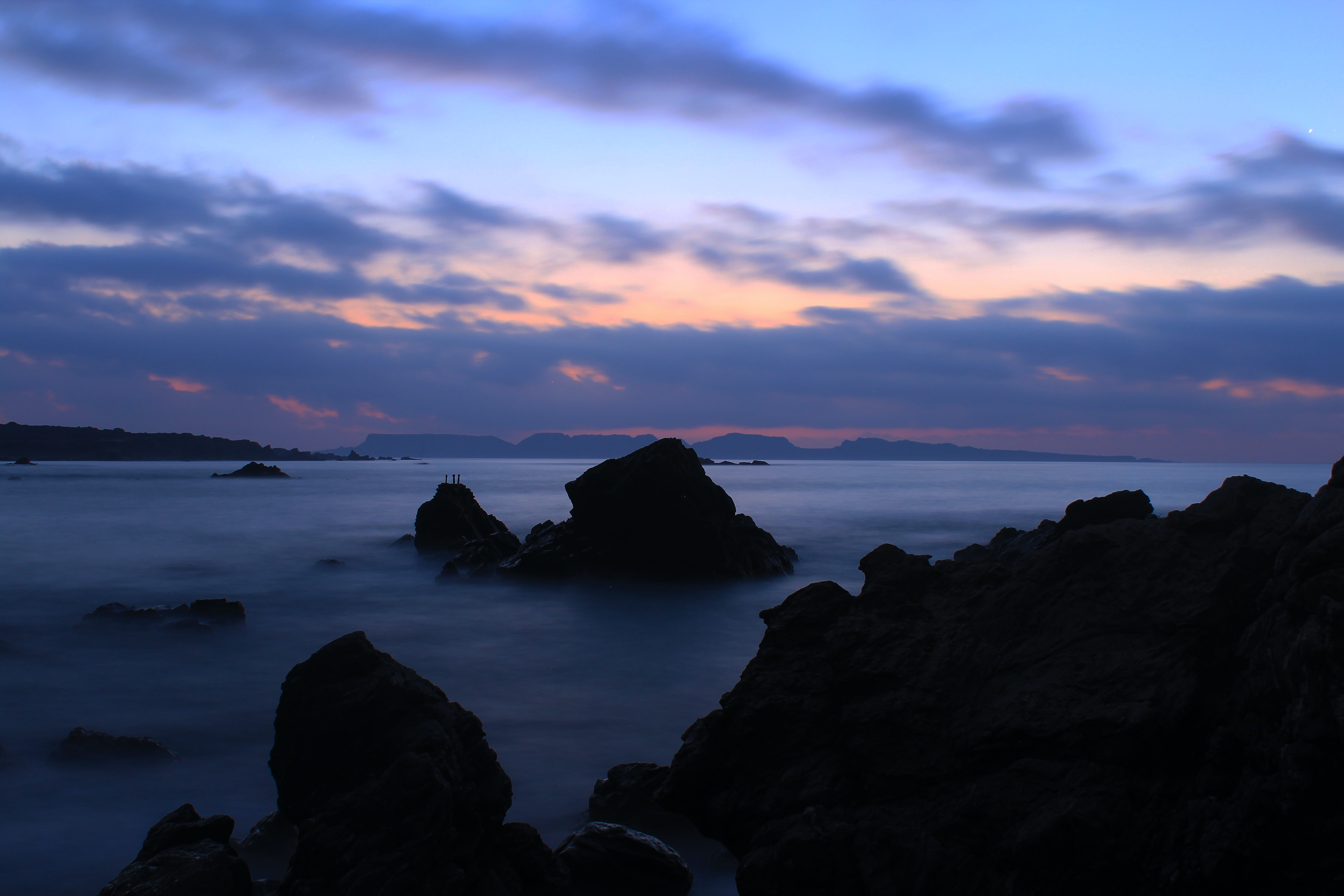 Cloudy sunset at Punta Choros with silhouettes of rocks in the ocean.
