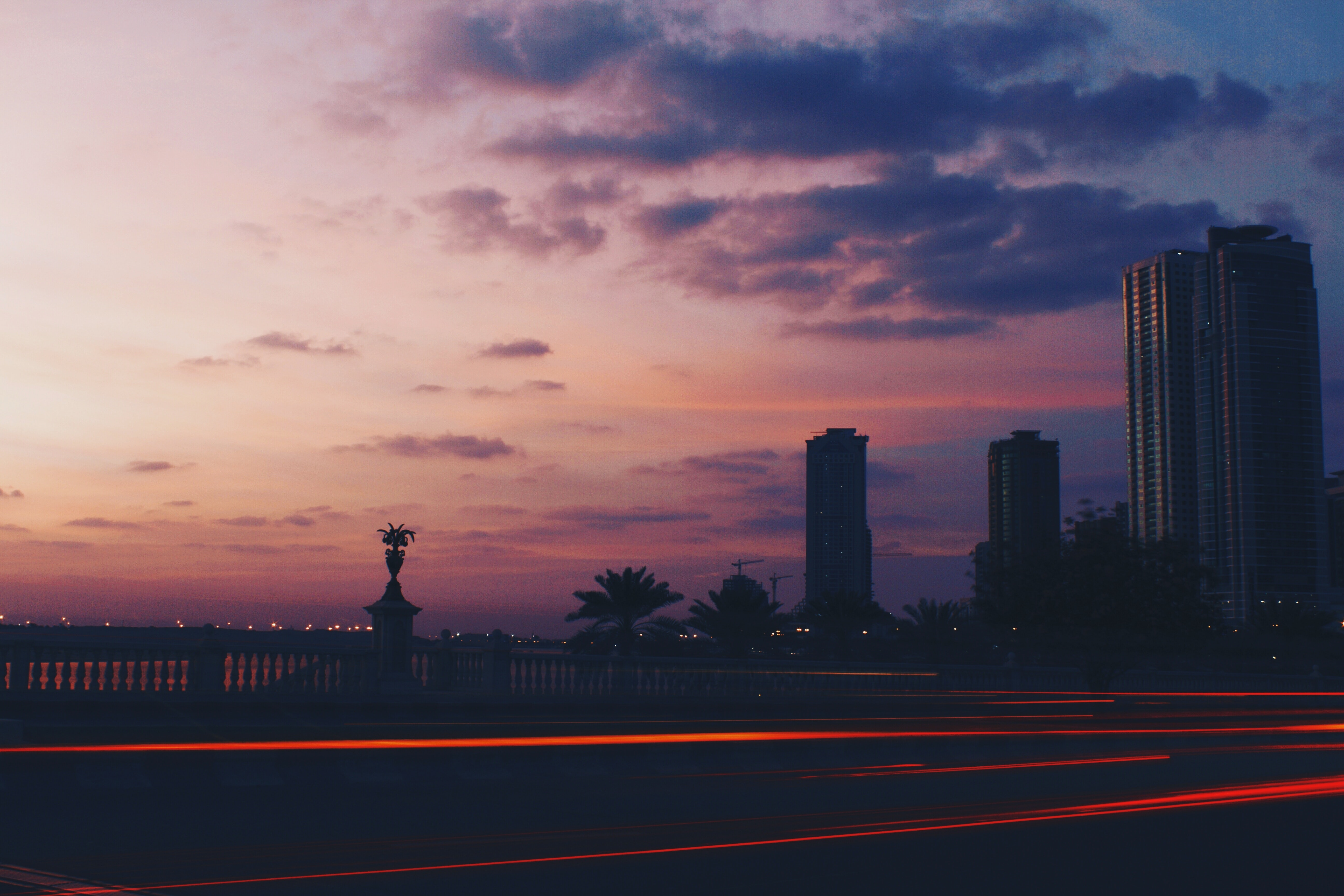 A city skyline, plants, and railing against pink and purple skies, red lights trailing with long exposure effect