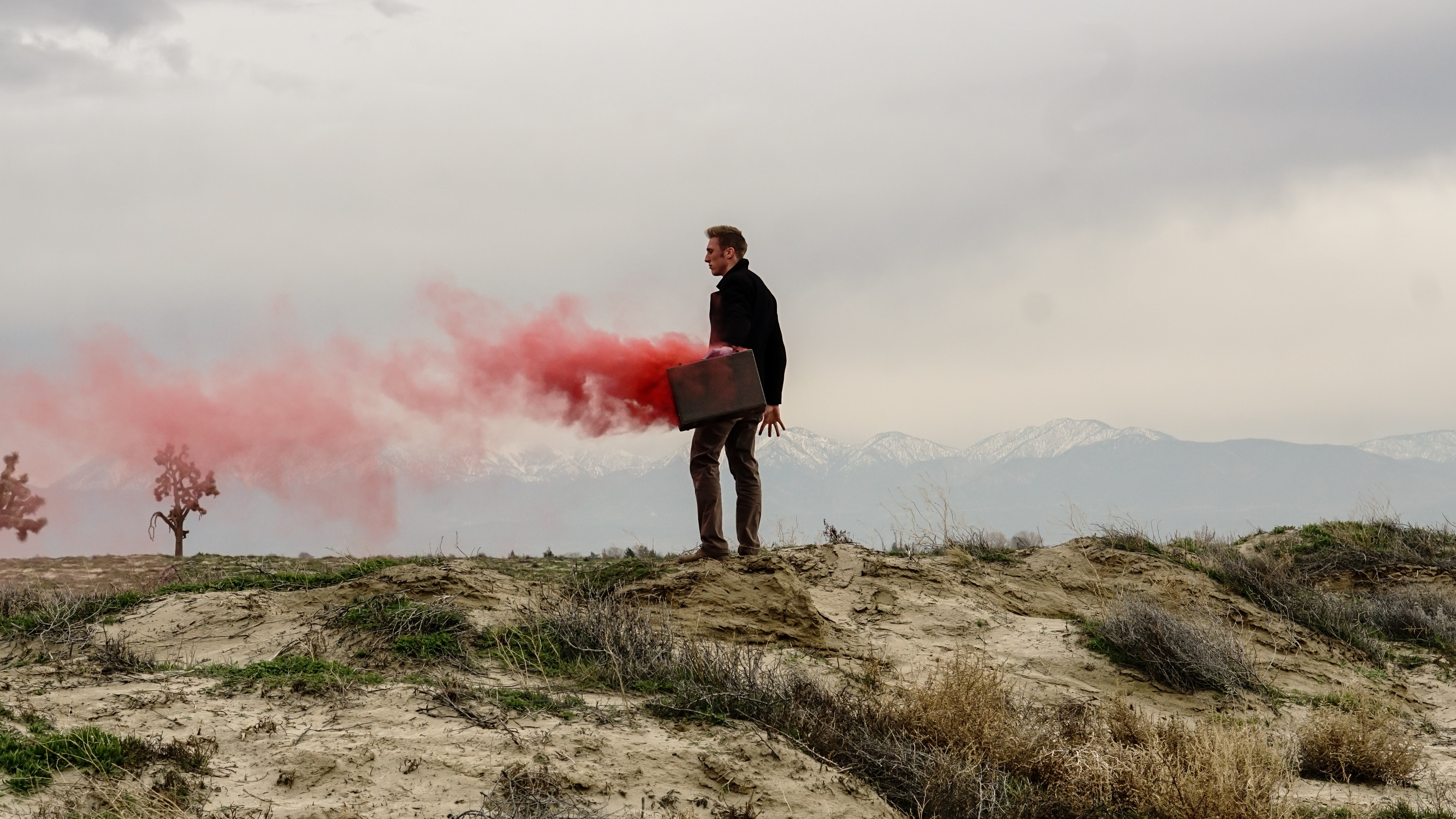 Red smoke escaping a briefcase, held by a business man at the edge of a cliff.