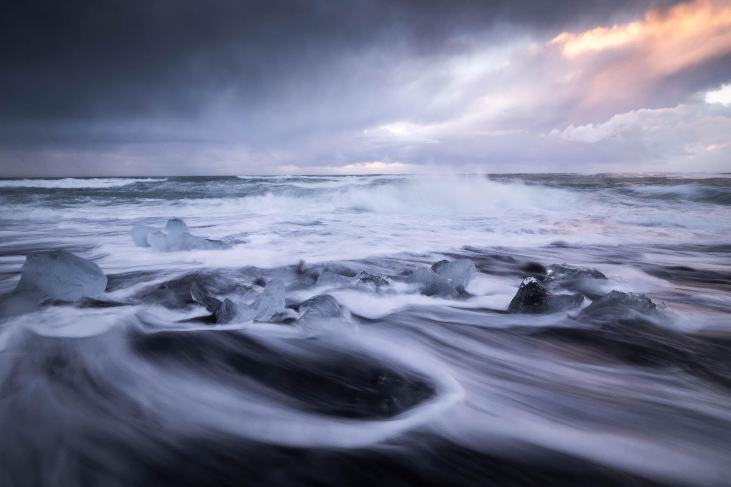 A cloudy sunrise above splashing sea waves in Jökulsárlón