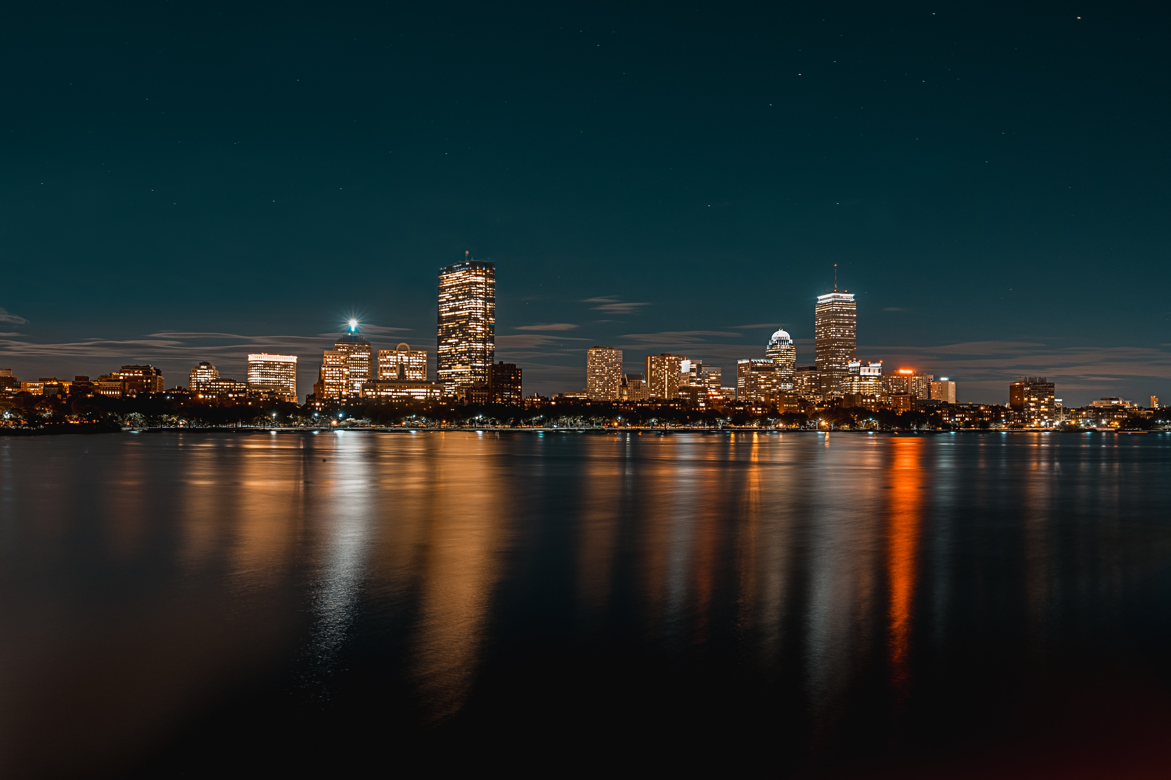city buildings next to body of water during nighttime