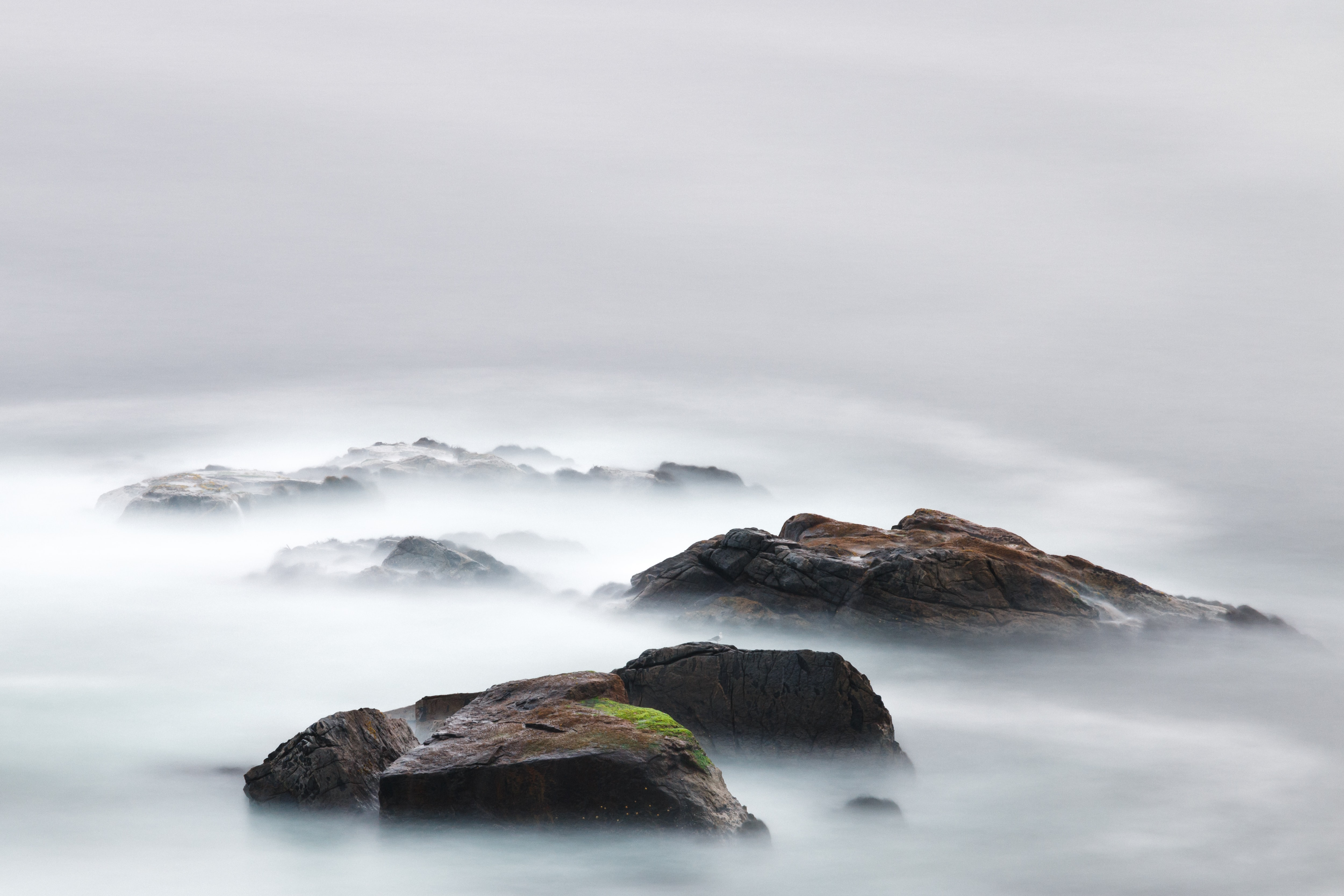 Wet rocks covered in mist on a gray and overcast day