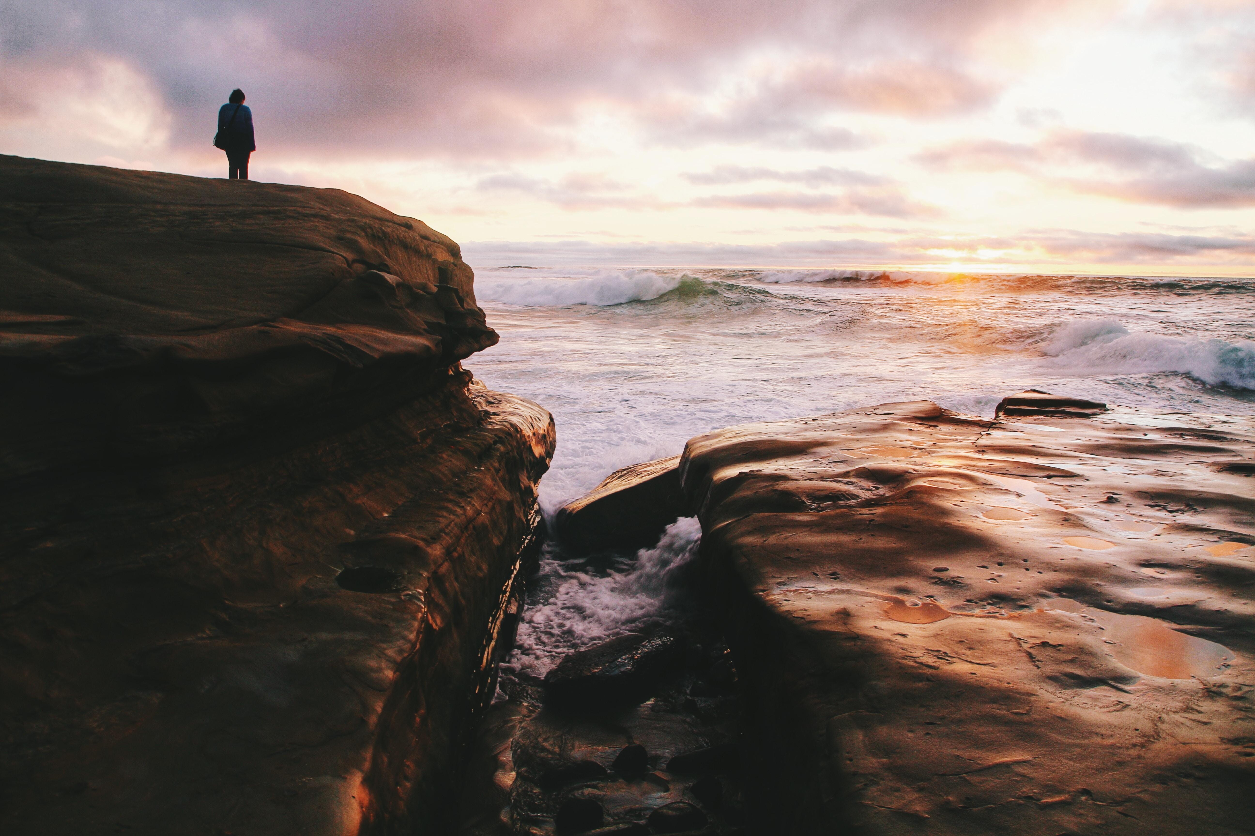 Silhouette person standing on coastline rock with white water ocean braking below