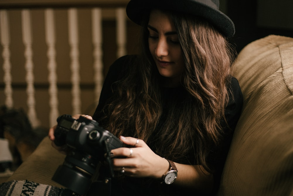woman holding DSLR camera sitting on brown chair