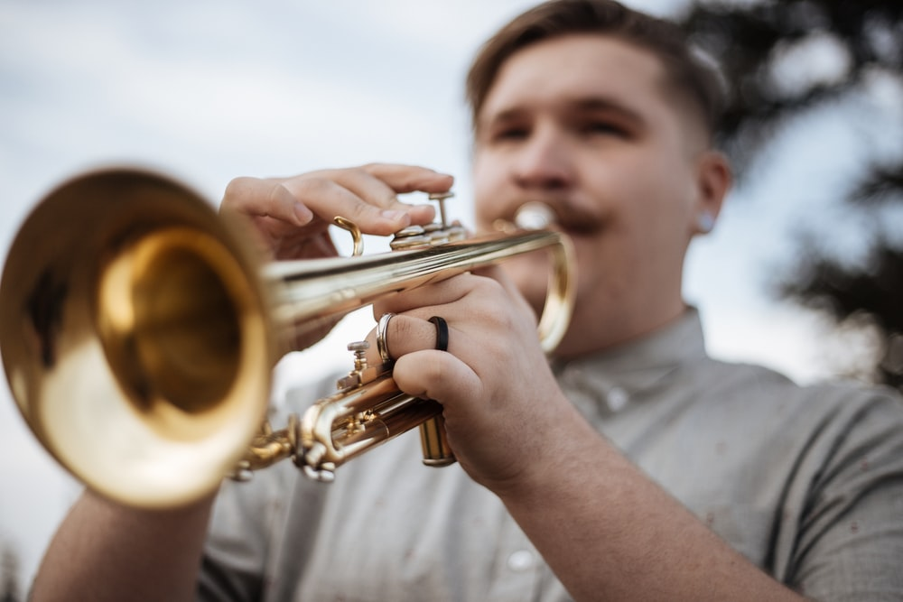 man playing trumpet outdoors
