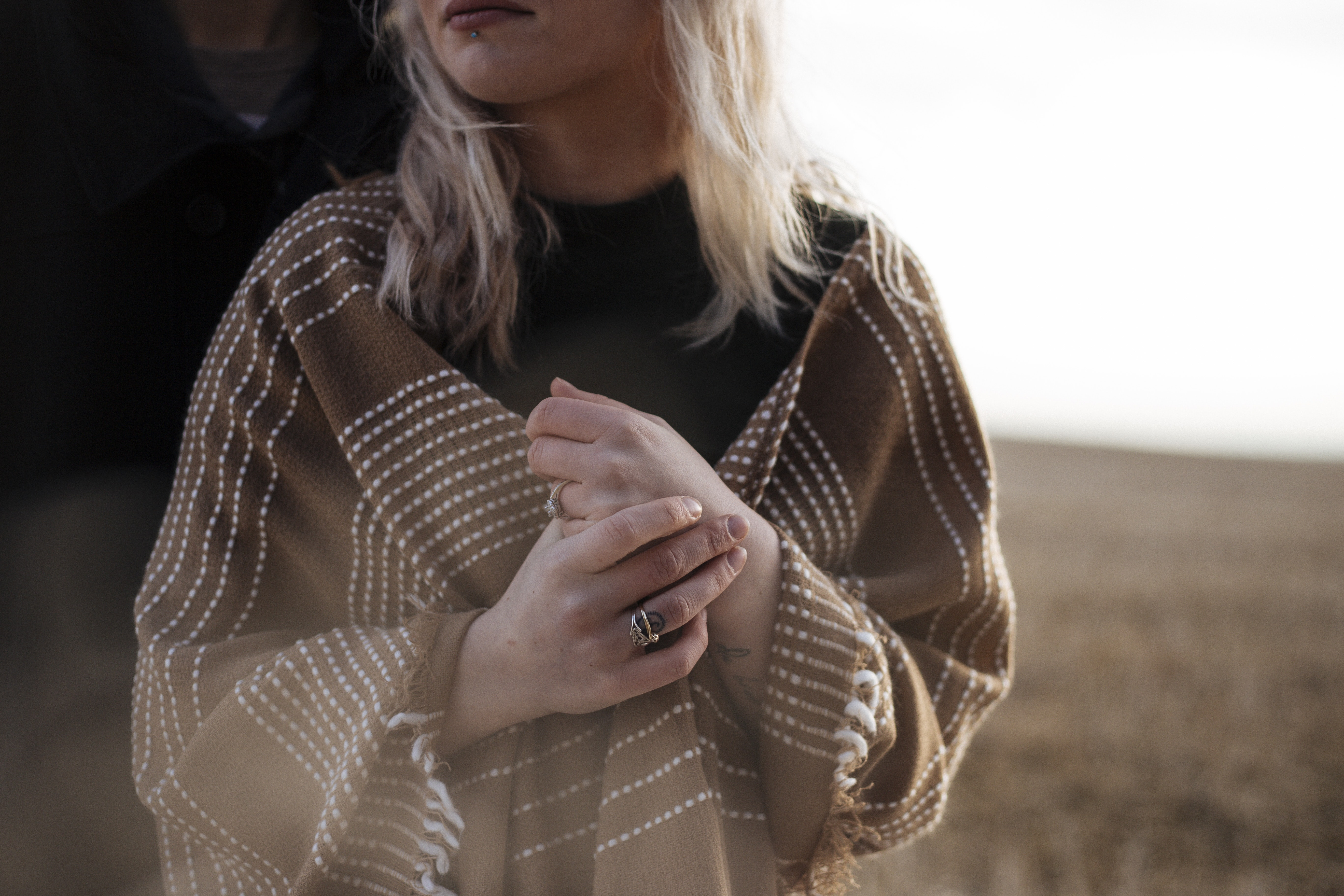 Torso of a woman wearing trendy rings and a brown shawl