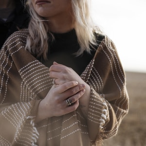 woman covered in brown scarf with cross hands