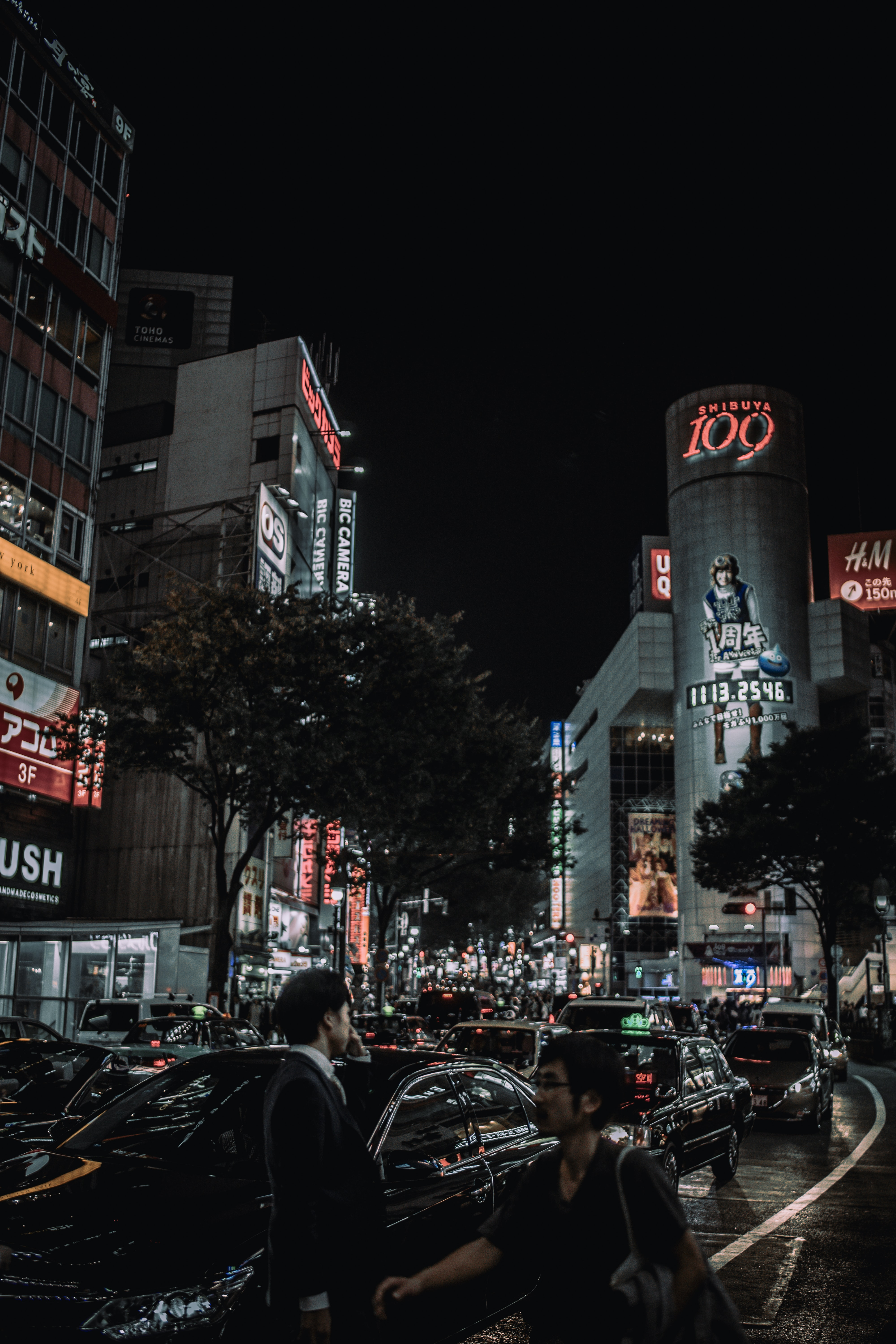 Busy urban streets with pedestrians and neon building store signs in Shibuya Crossing at night