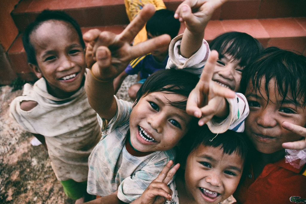 five children smiling while doing peace hand sign