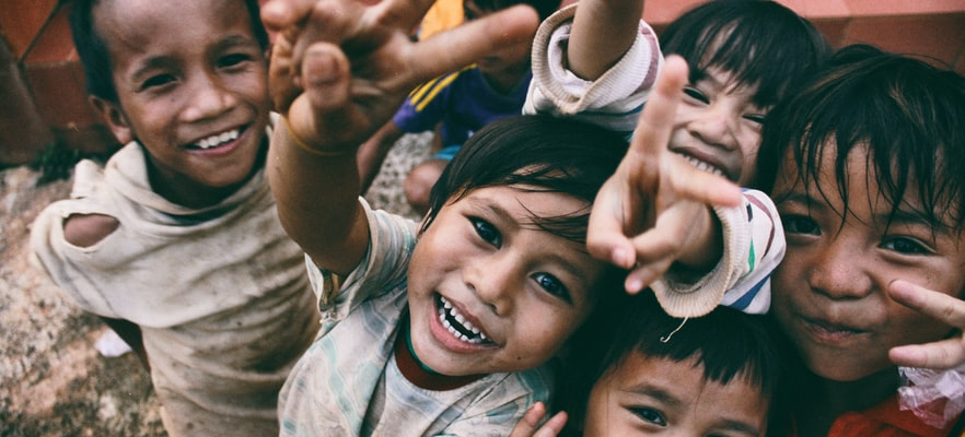 Children looking up at a camera, smiling and gesturing at it