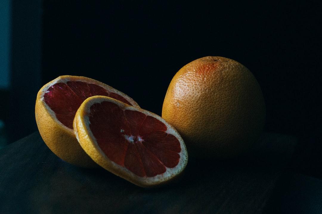 Slices of fresh grapefruit on a black backdrop