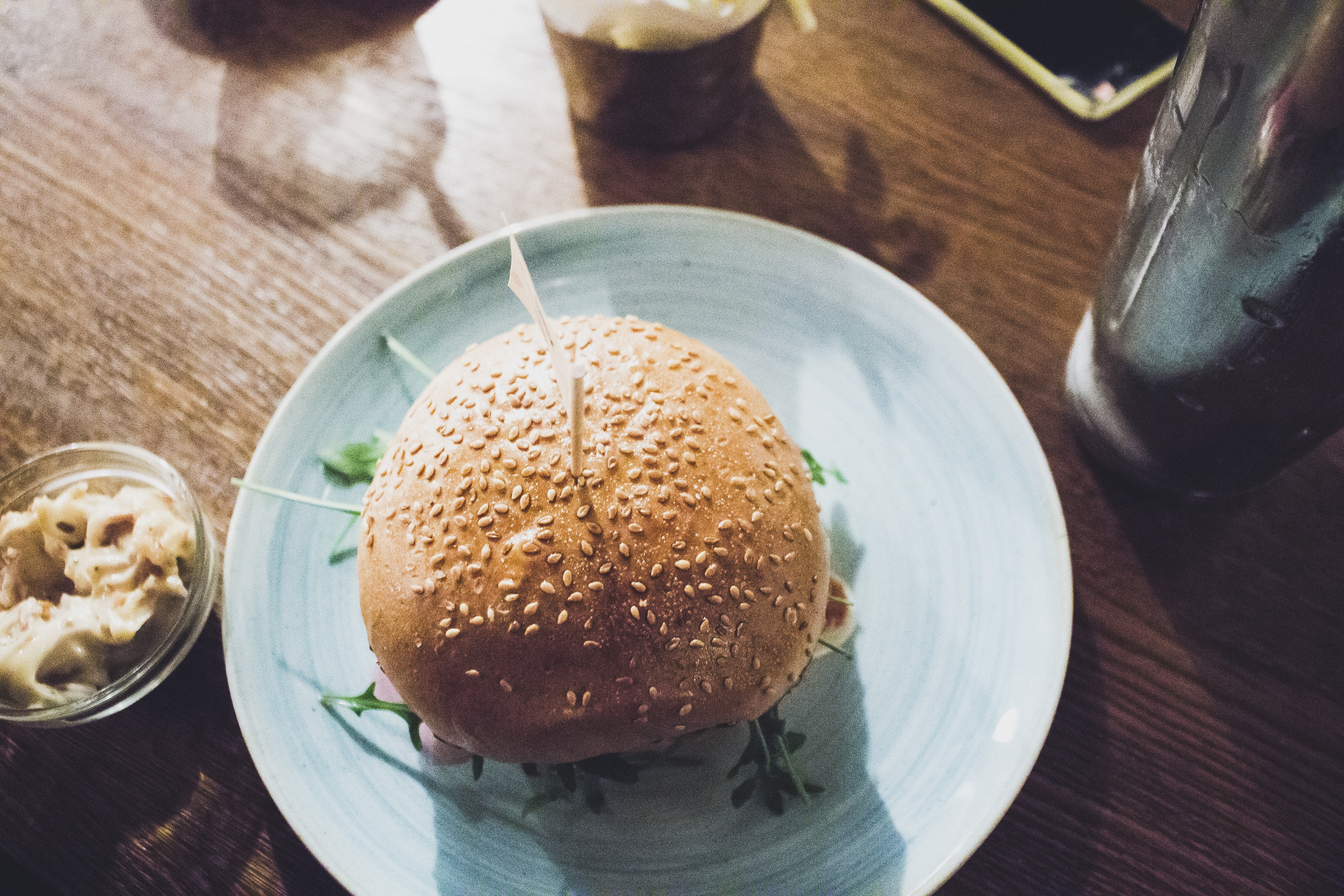 Burger with a sesame bun on a light blue plate