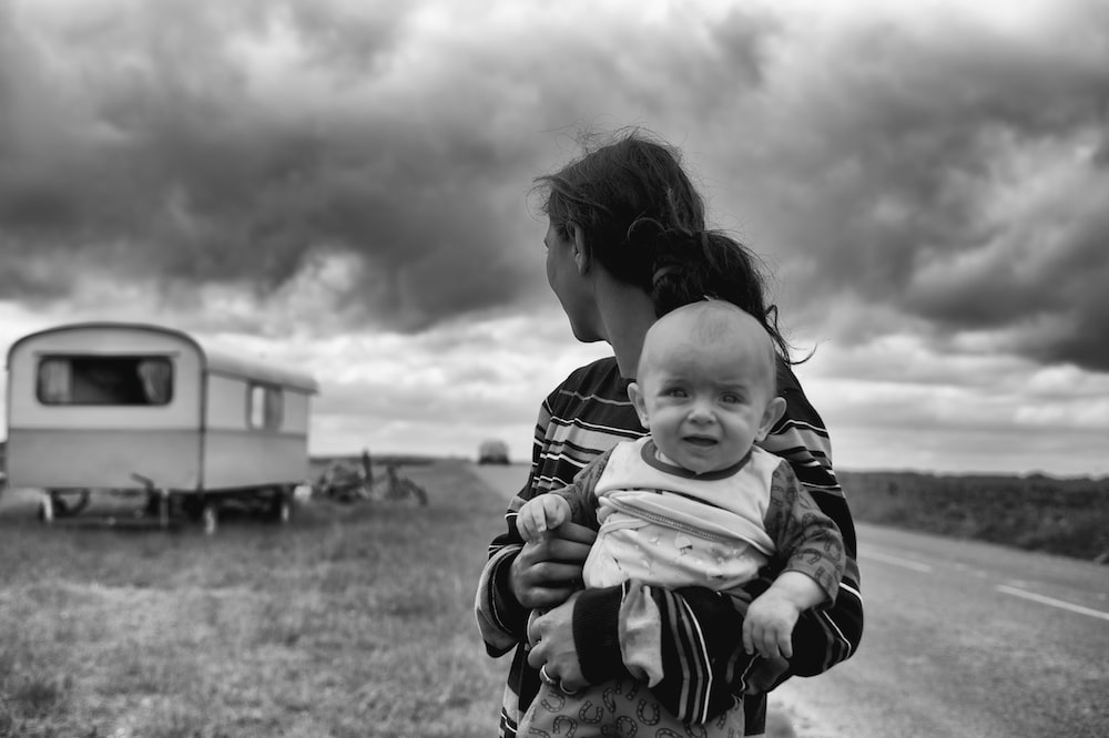 gray scale photography of woman carrying baby looking at camper trailer