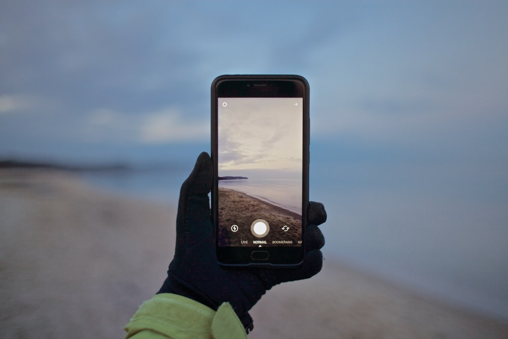 person black smartphone taking picture