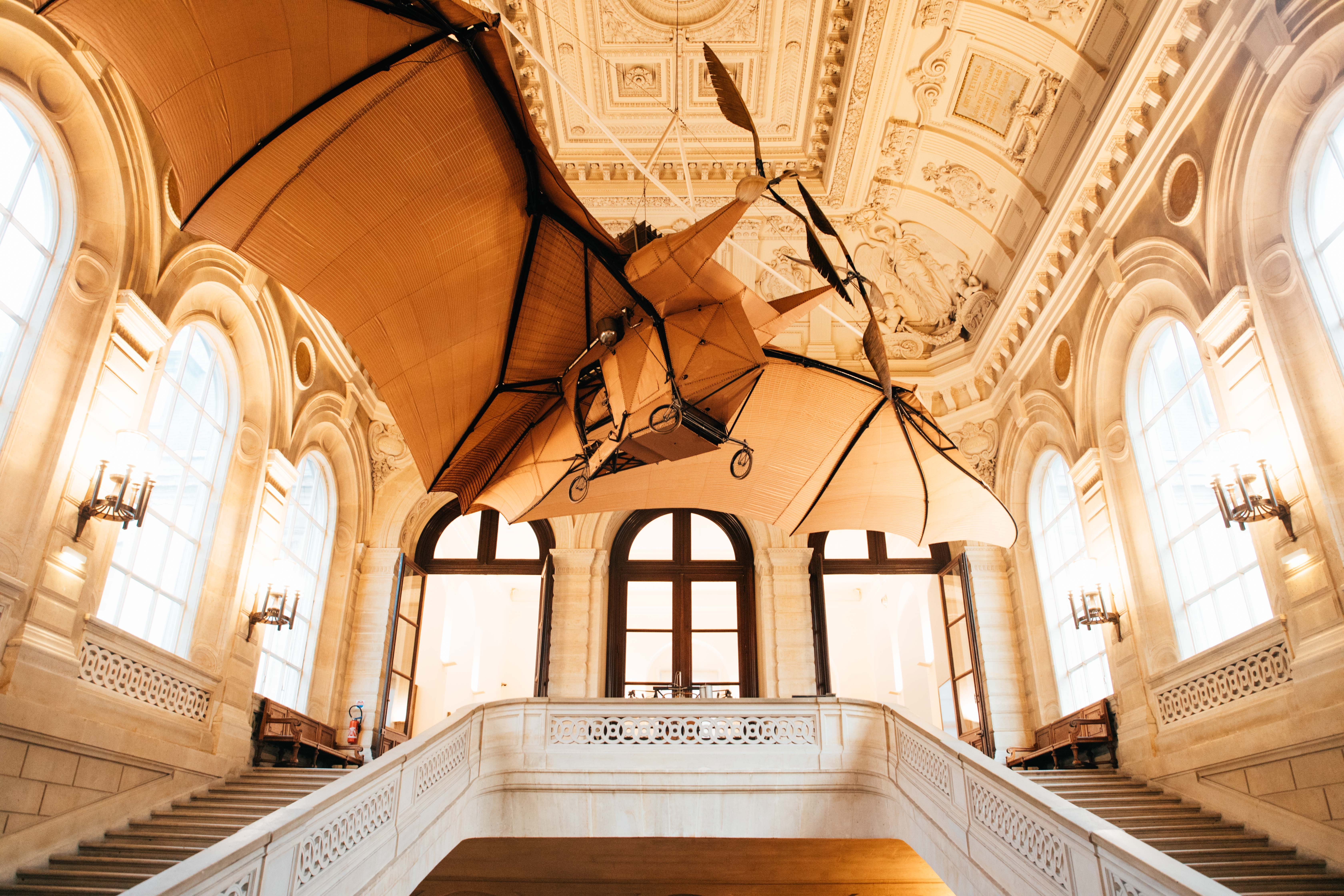 Ornate stairwell and ceiling architecture with flying machine at Metiers Art Museum