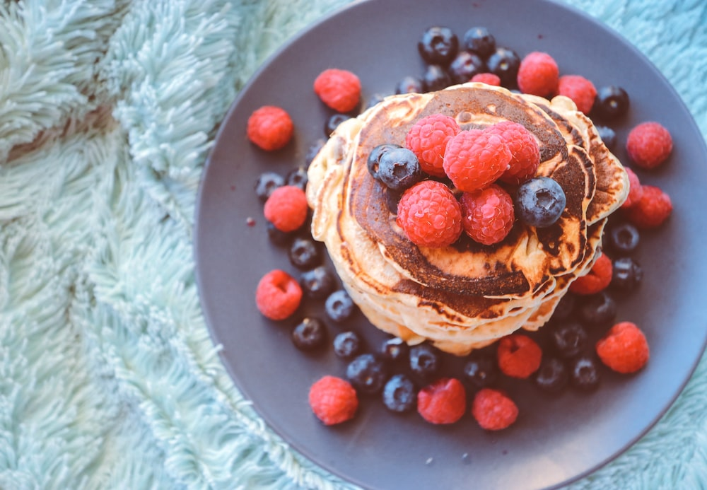 pancakes with blueberries and raspberries on gray plate