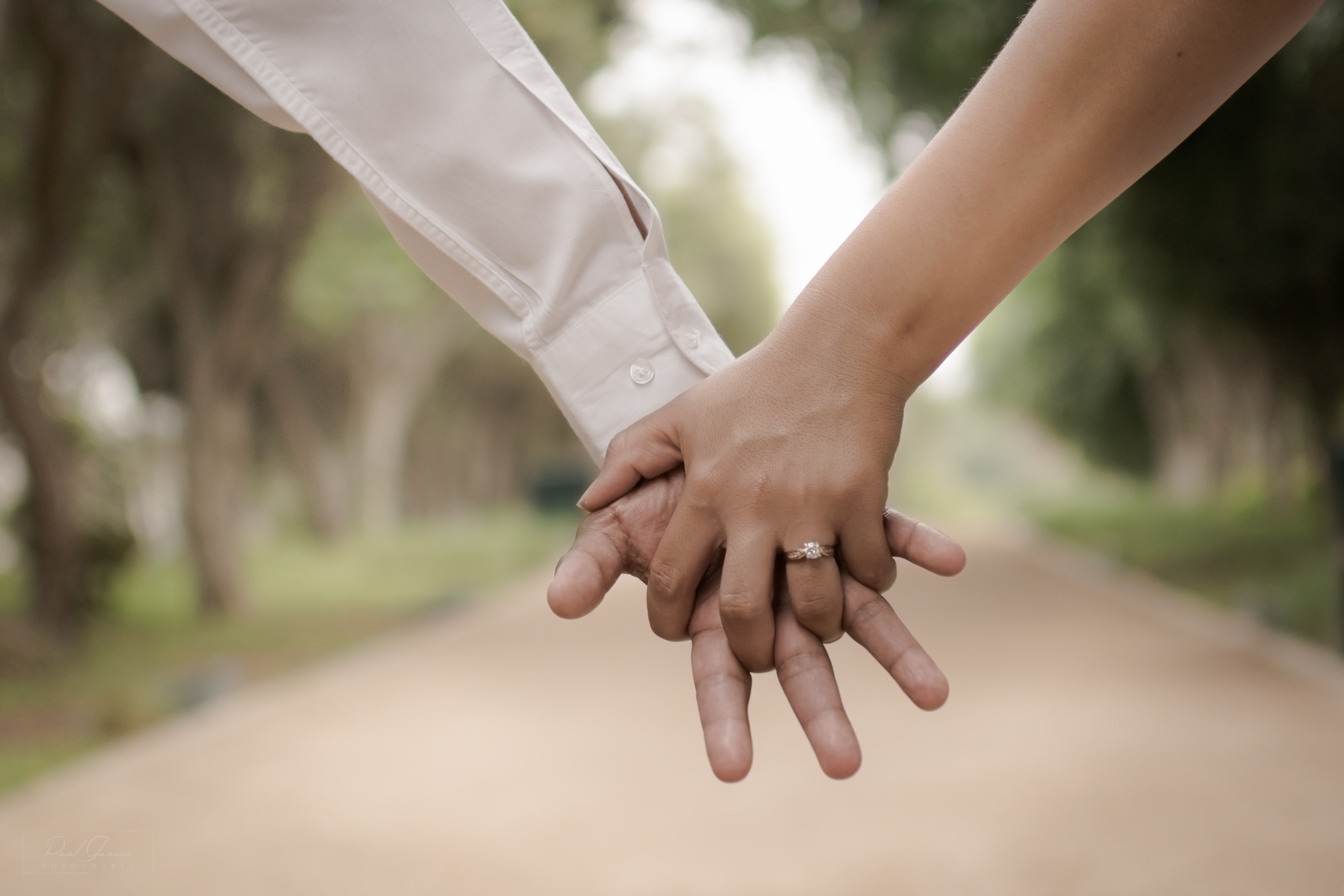 Close-up of an engaged couple holding hands outdoors. One wears a long-sleeved shirt.