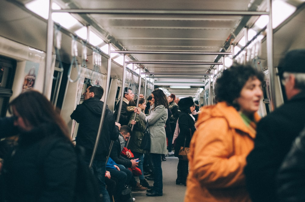 woman standing inside train surrounded by people