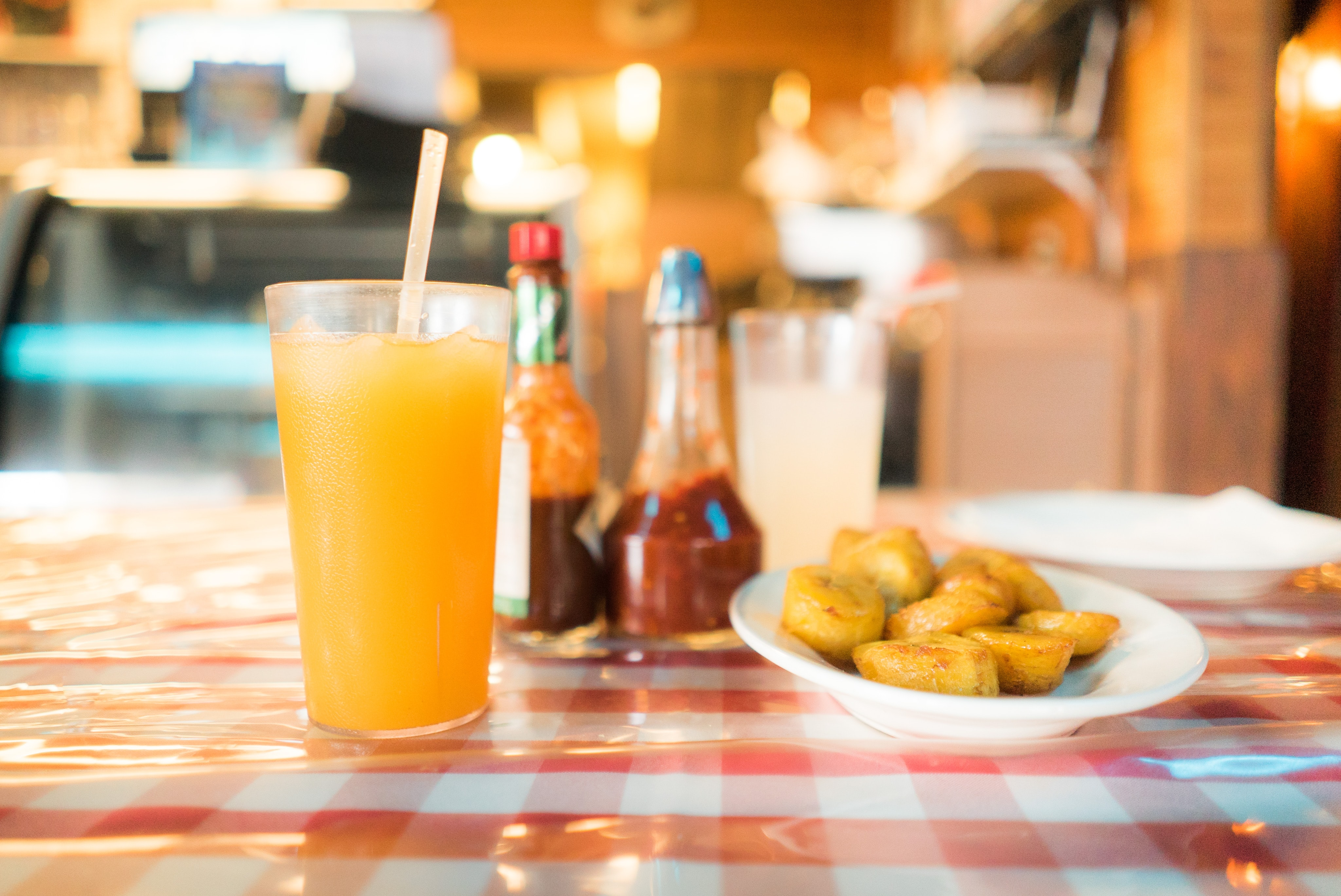 Fried potatoes next to a glass of juice and sauce bottles on a restaurant table