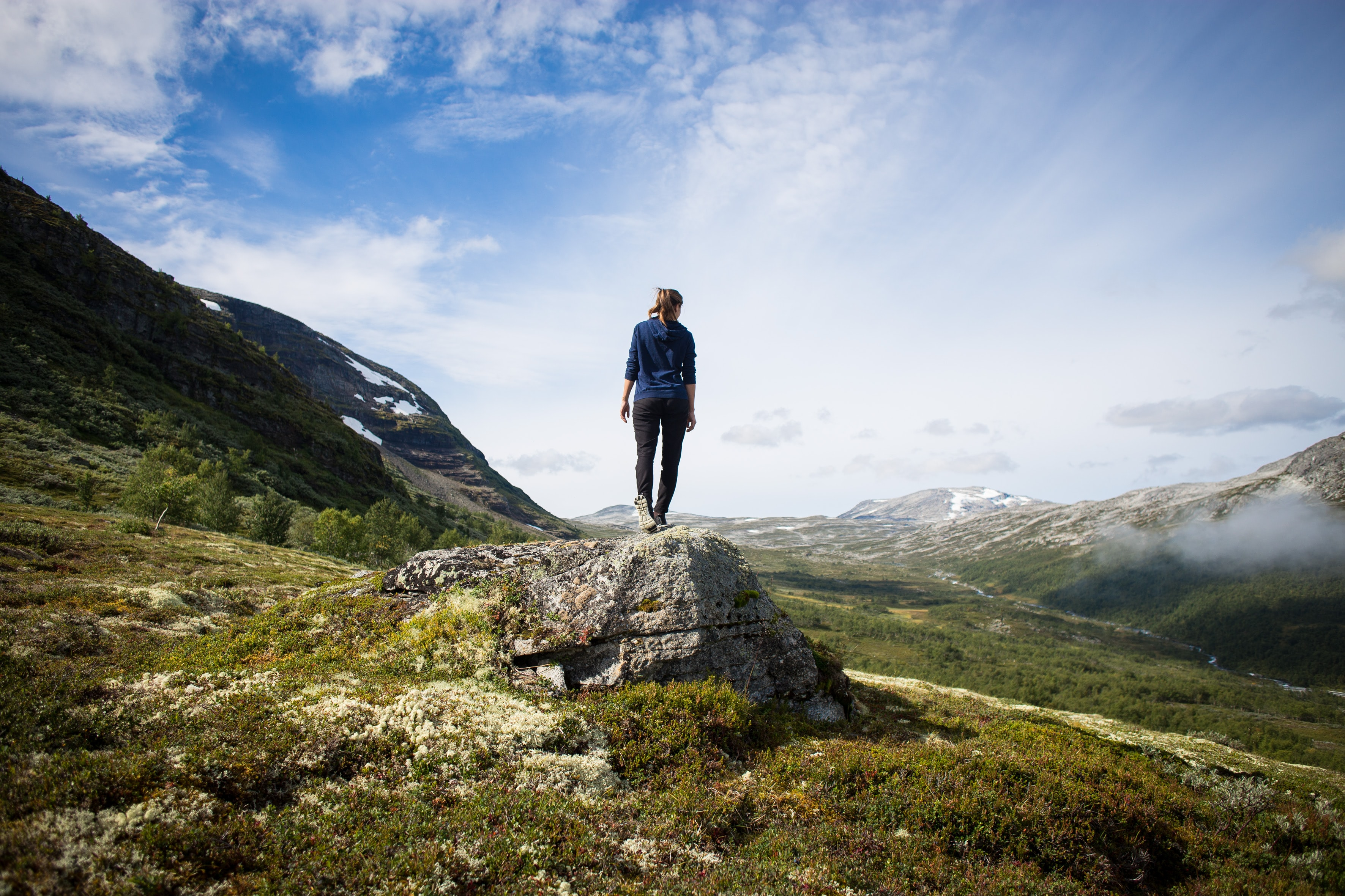 person standing on rock looking at mountain