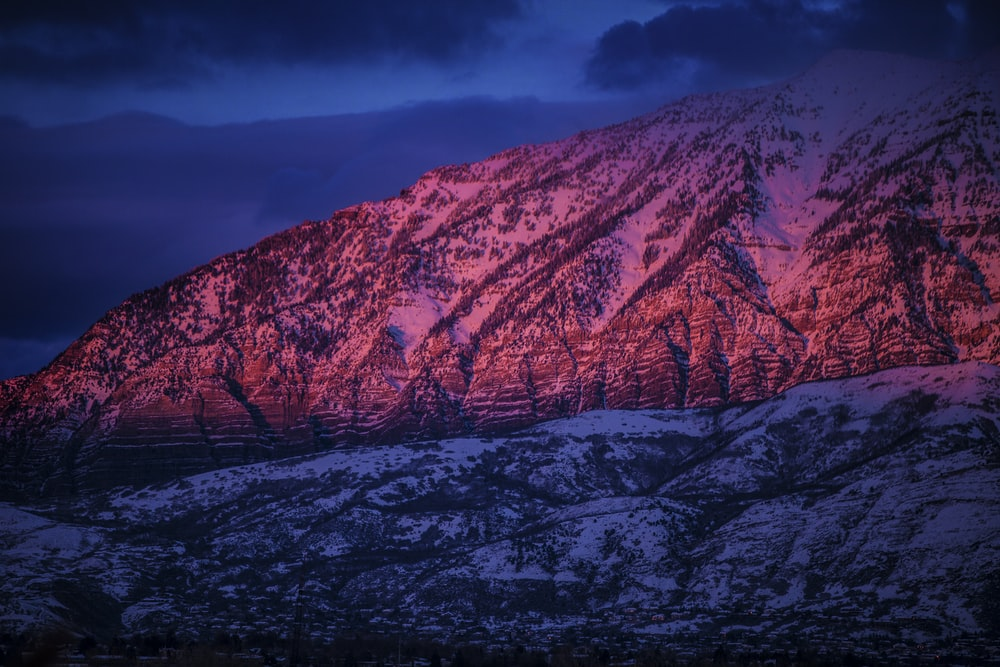 snow-covered mountain under cloudy sky during nighttime